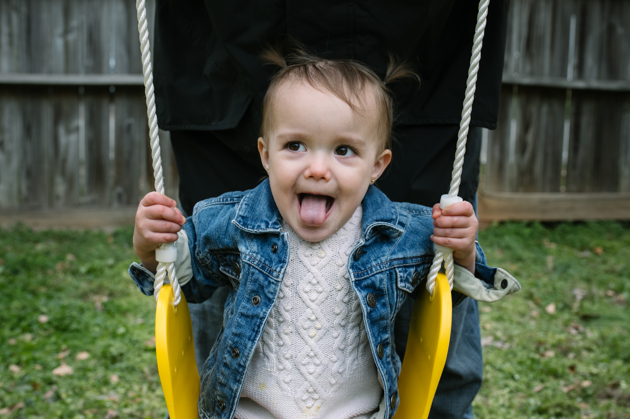 a toddler sits on a swing with her tongue out