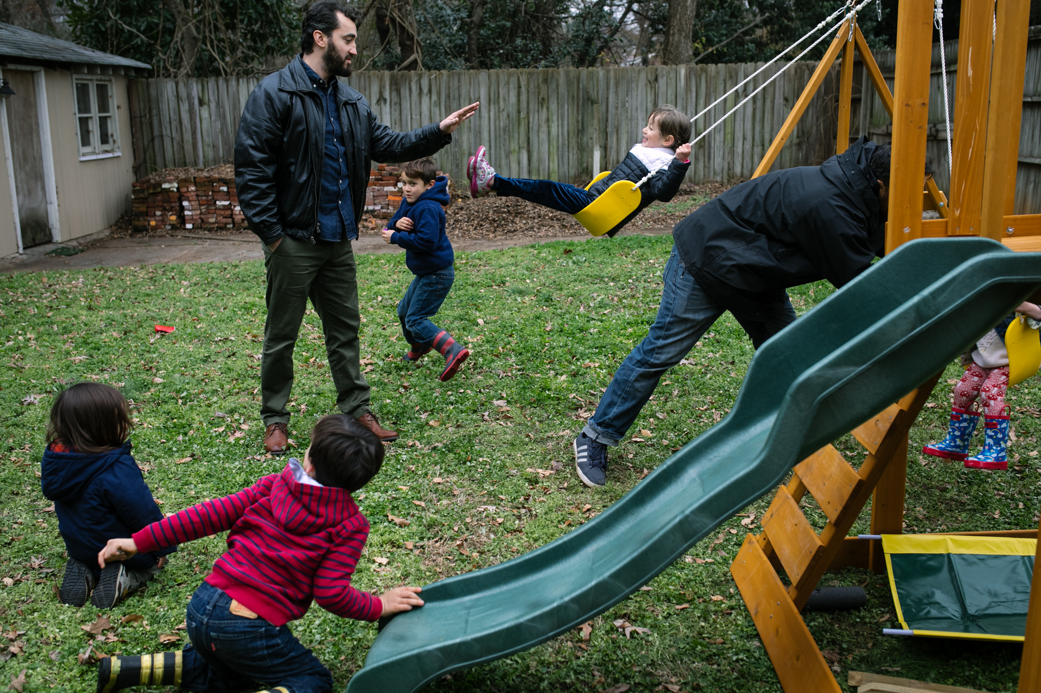 Several kids play on and around a playset while two dads push kids on swing