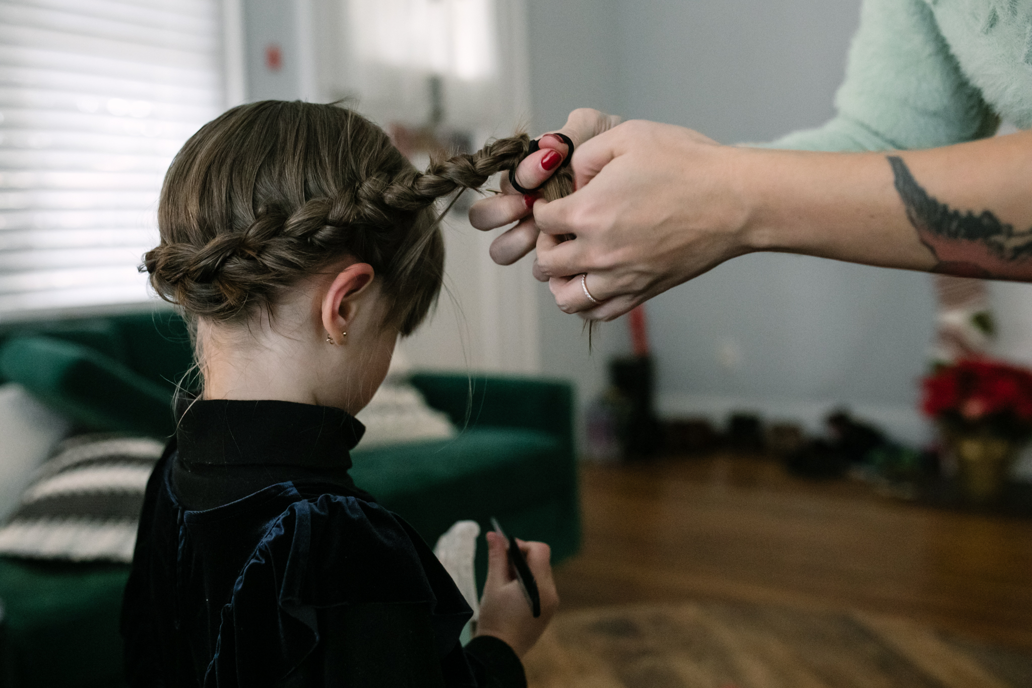 A mother ties the end of a crown braid she has made on her daughter's hair