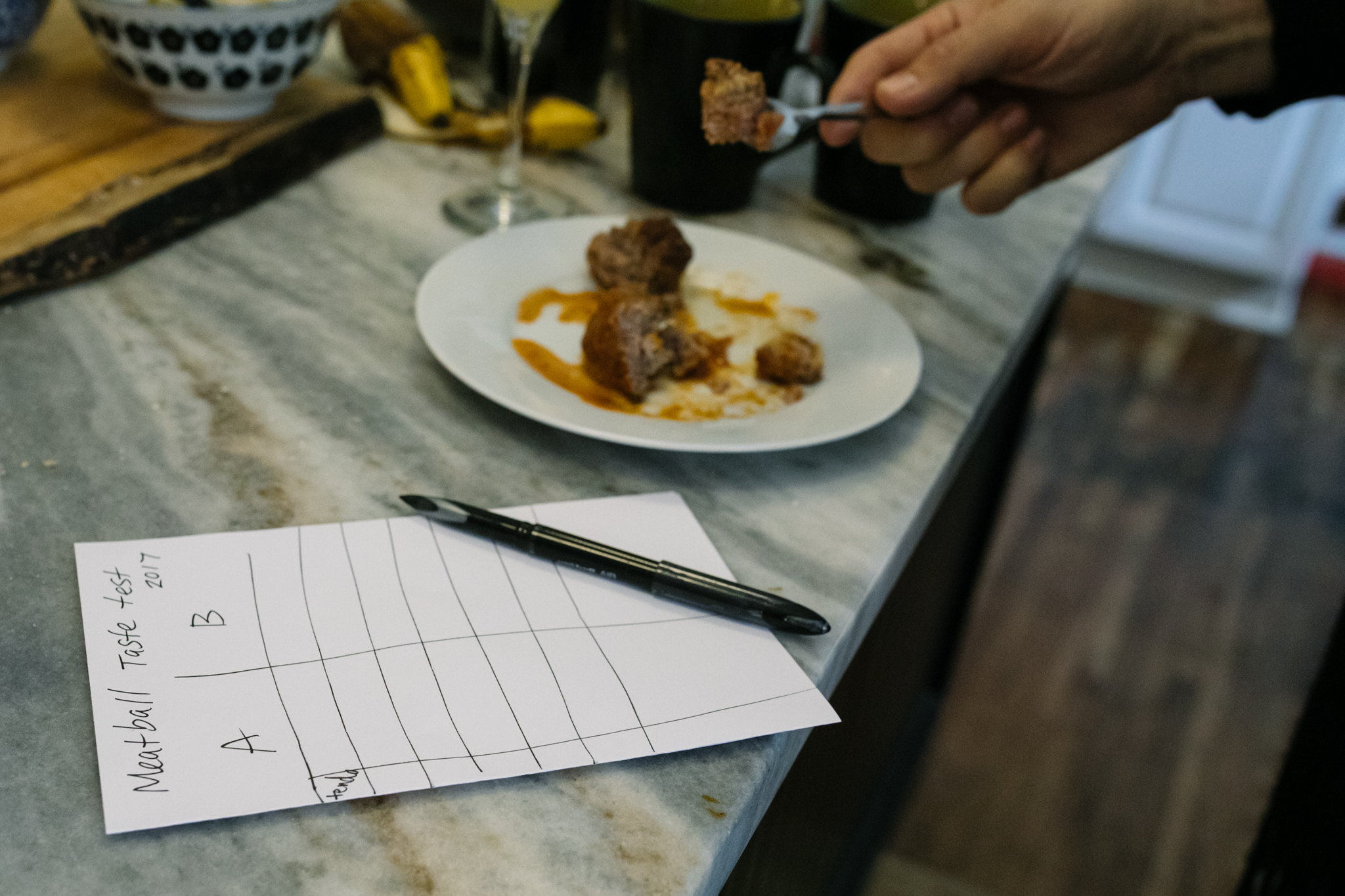 A score card sits next to a plate of meatballs on a kitchen counter
