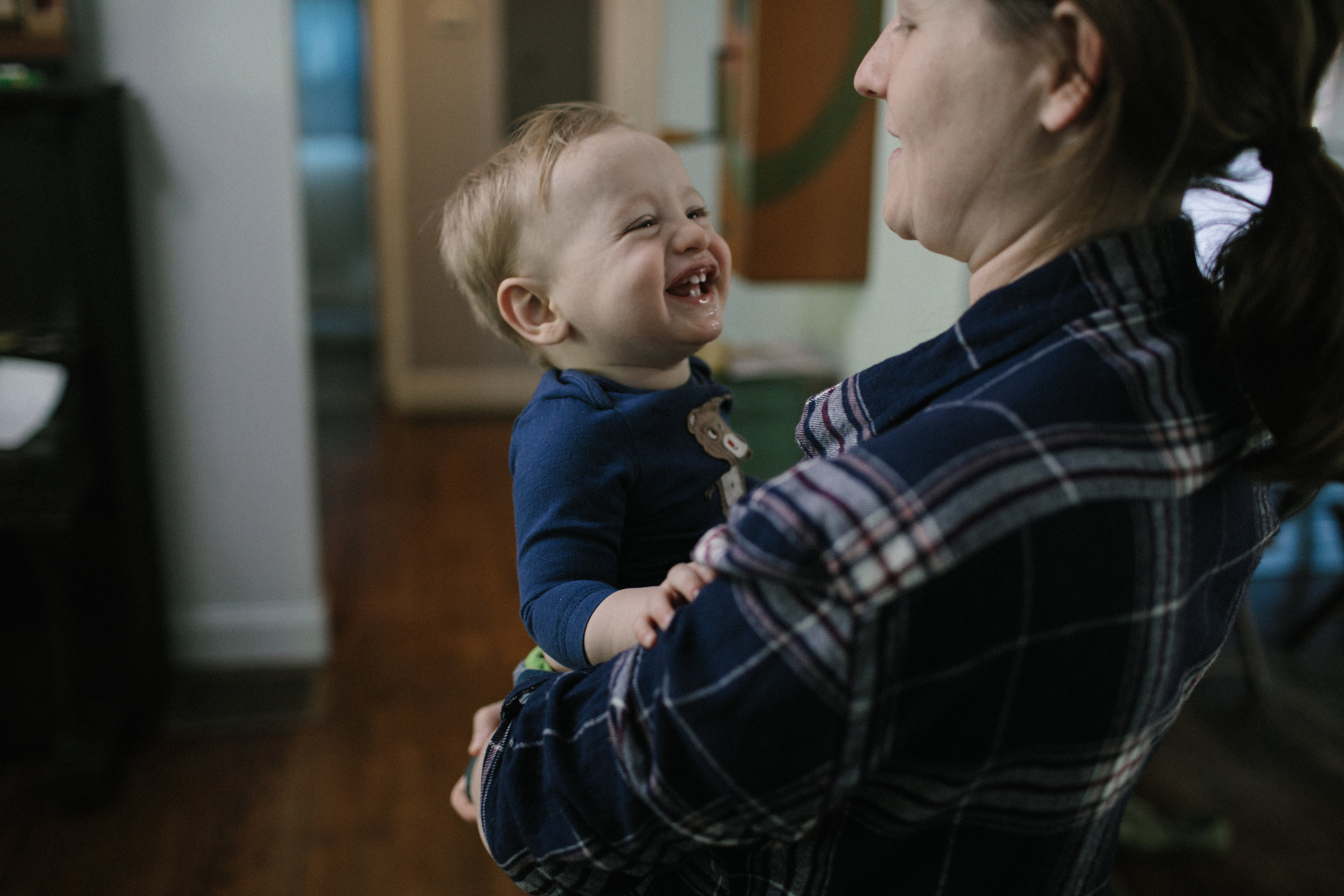 son smiles at mother who is holding him