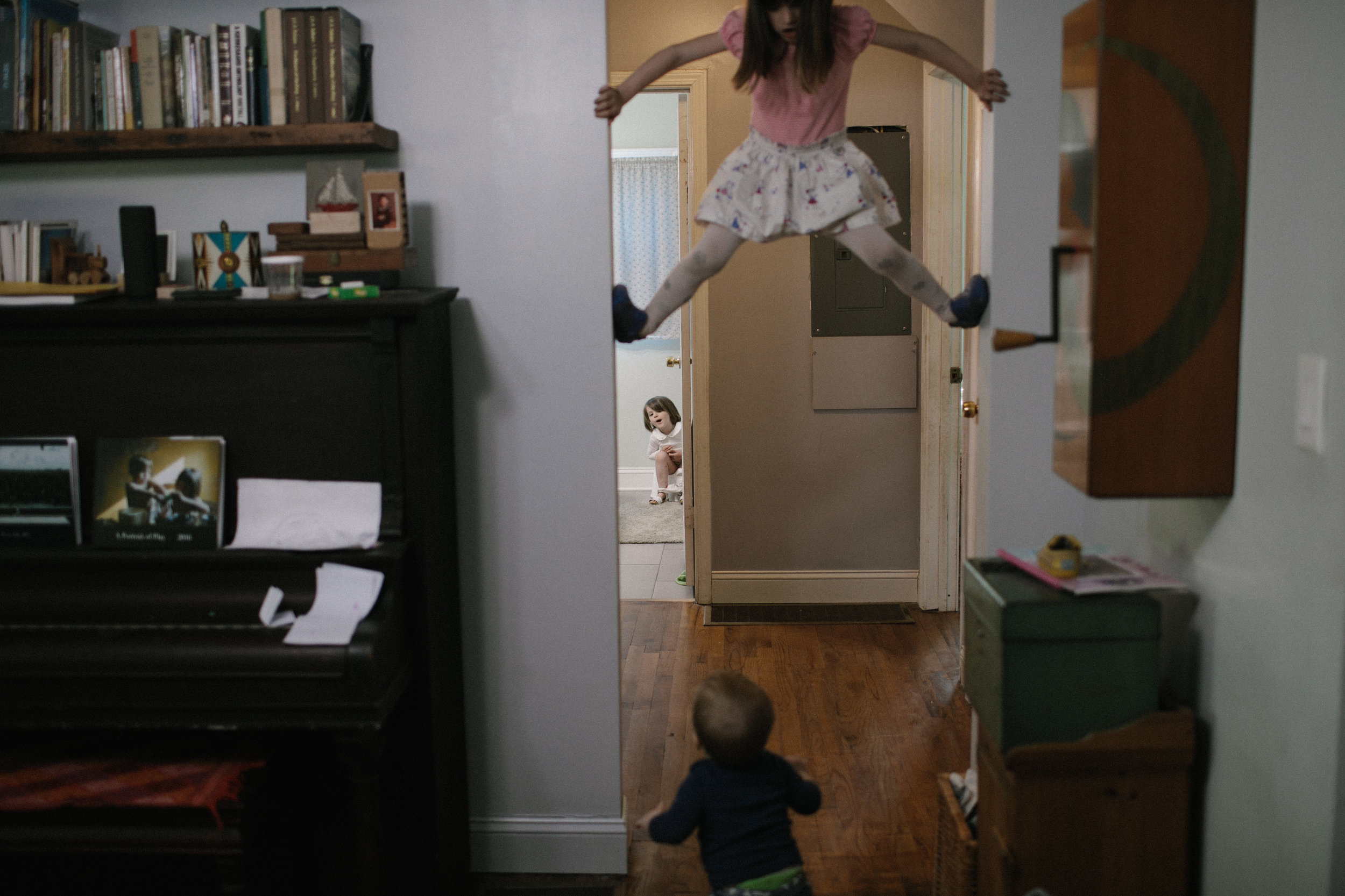 a child climbs a doorway while two other children watch