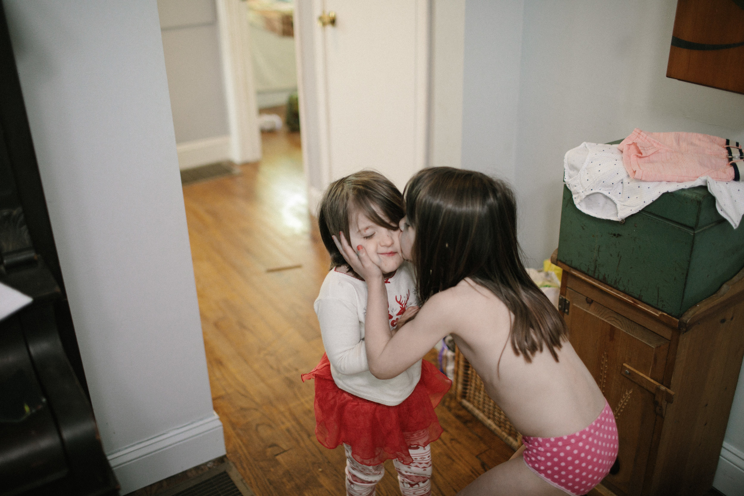 a child kisses her sister