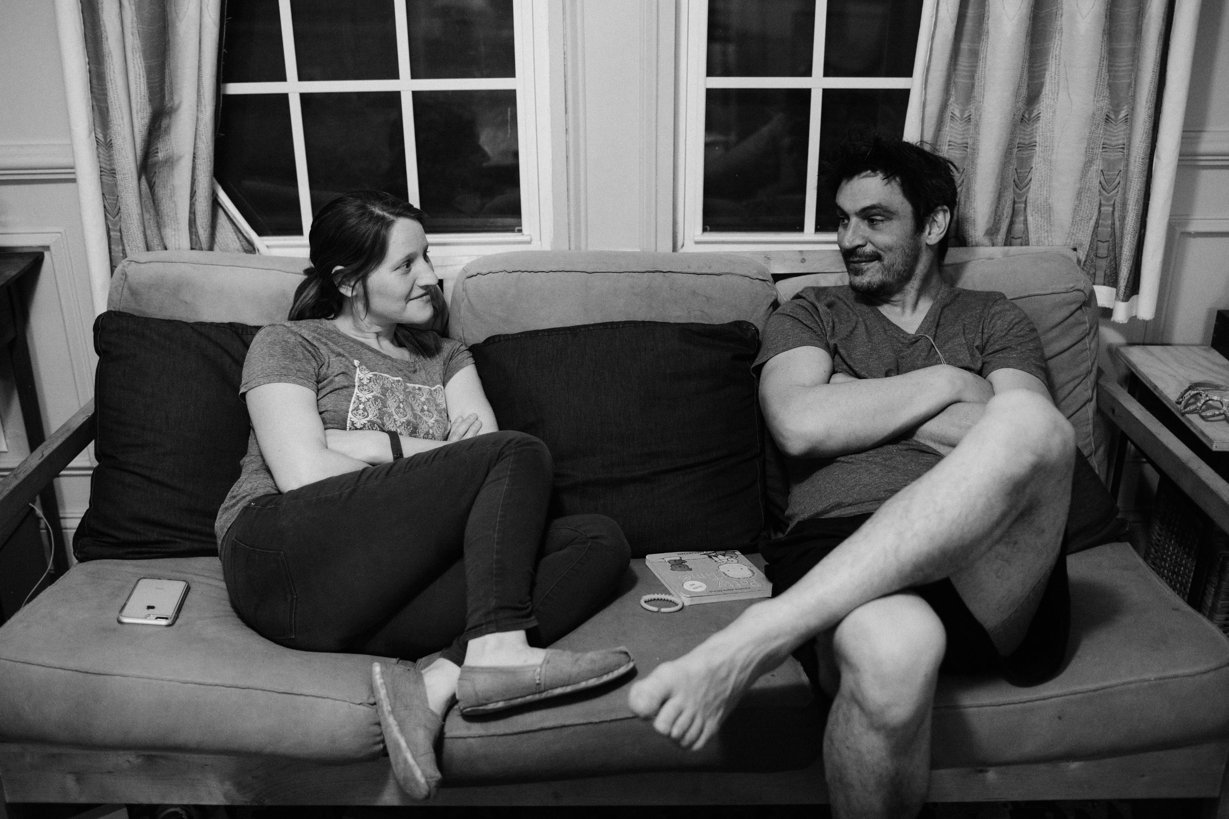 a couple sits on the couch and looks at each other