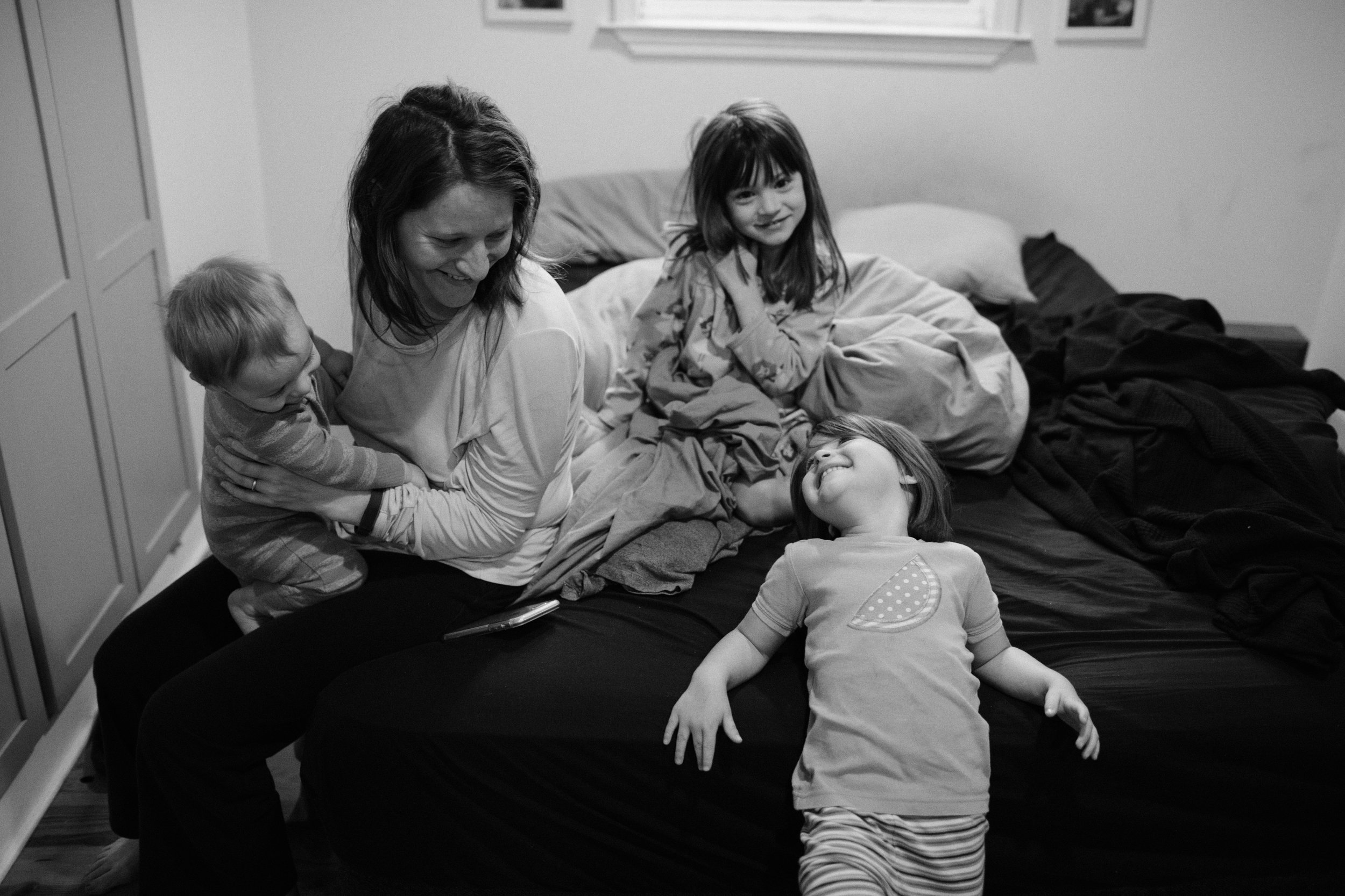 a mother sits on her bed with three children