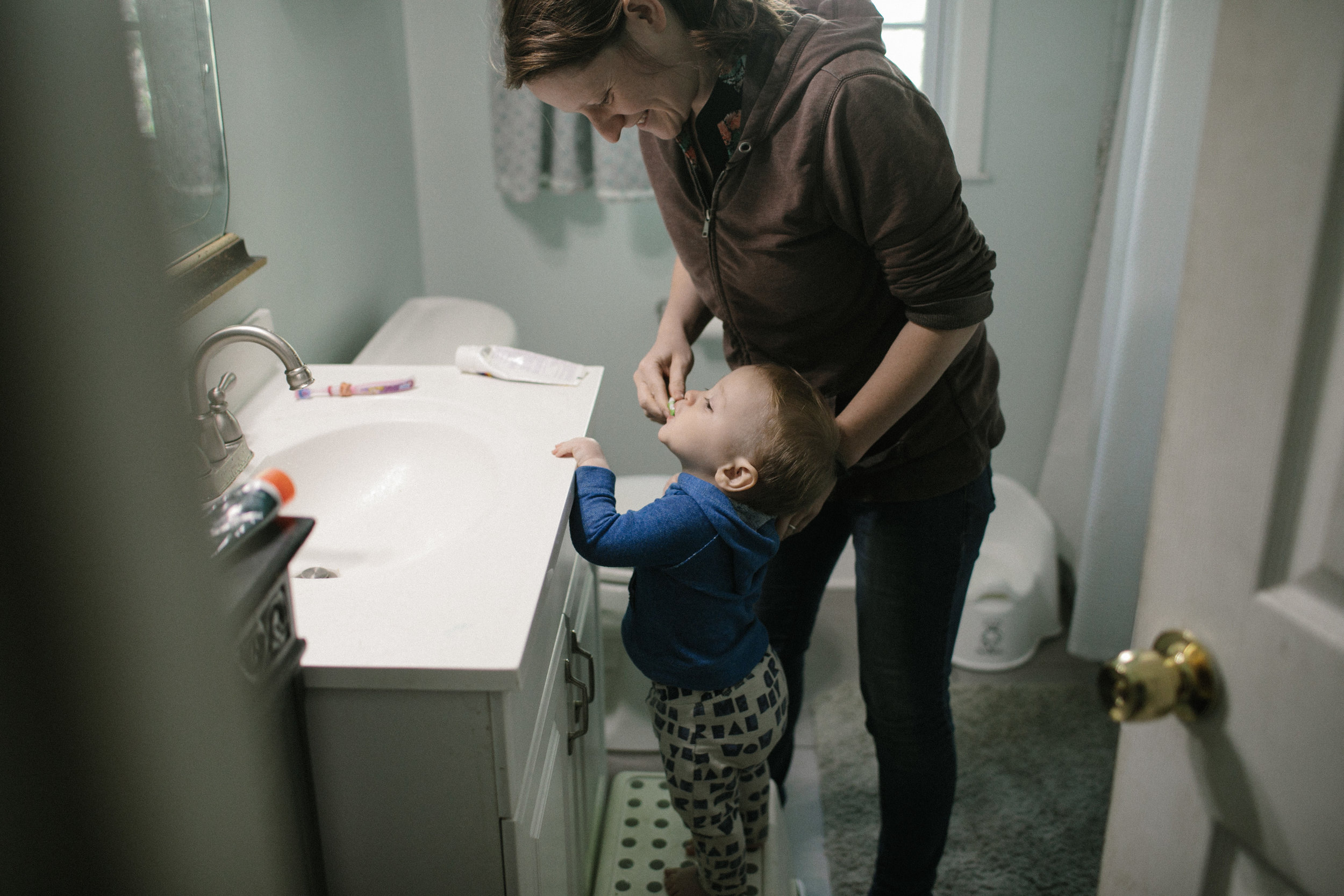a mother brushes her toddler's teeth