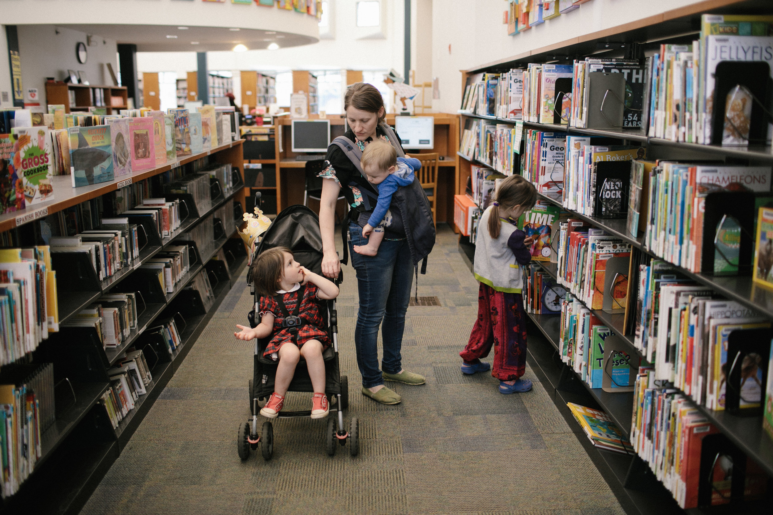 a mother wears a baby in the library as a child sits in a stroller and another one looks at a book