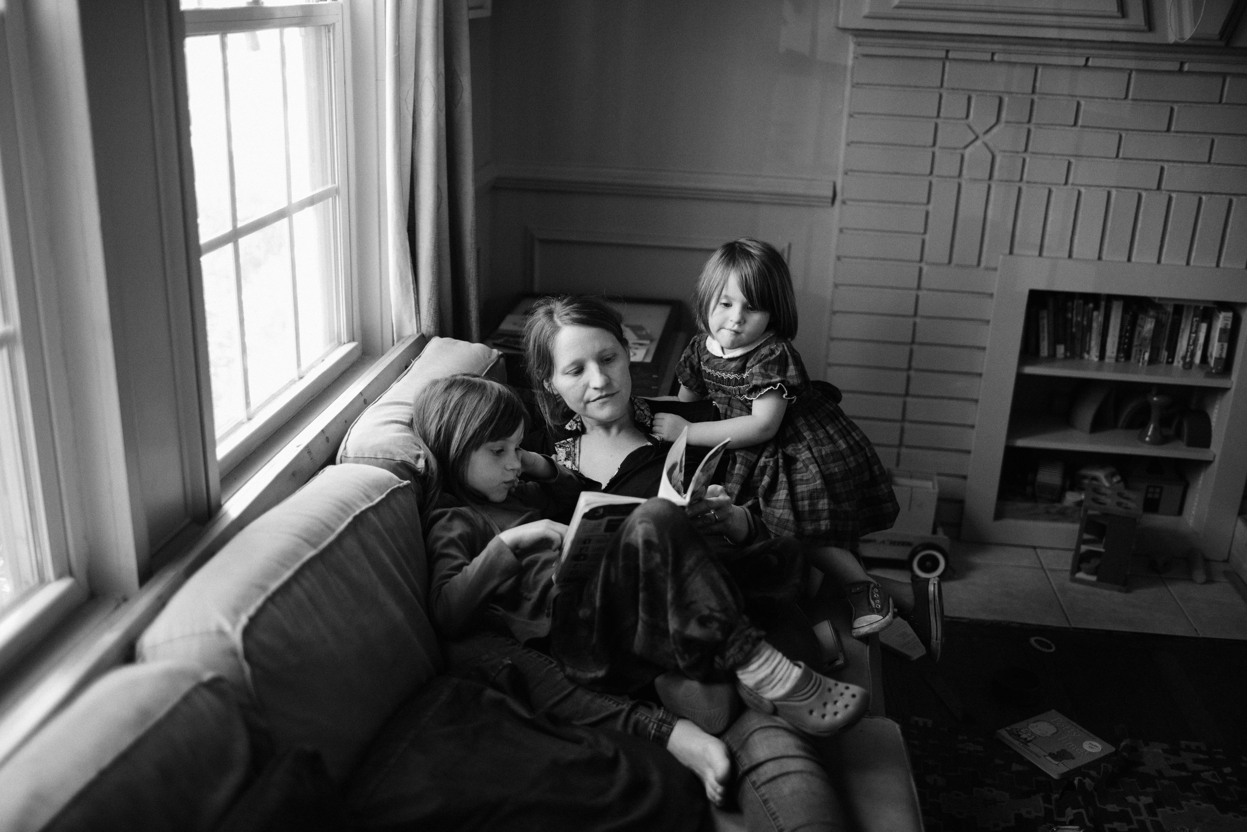 a mother and two daughters read on the couch