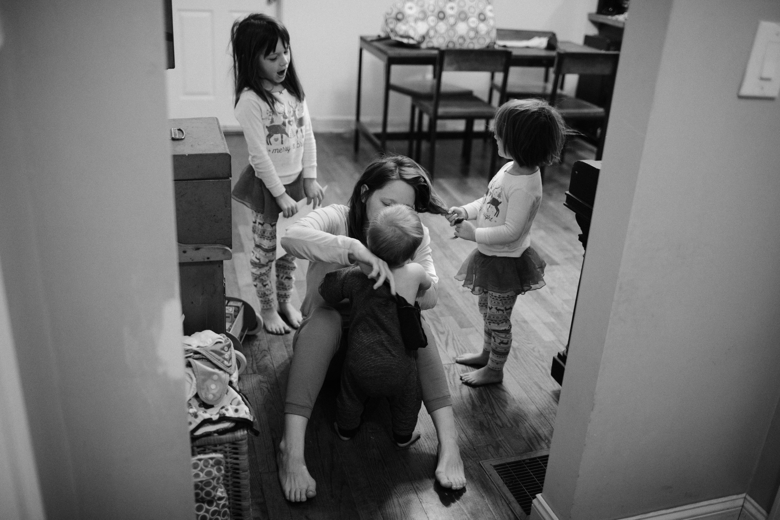 a mother dresses a baby while her daughter holds her hair