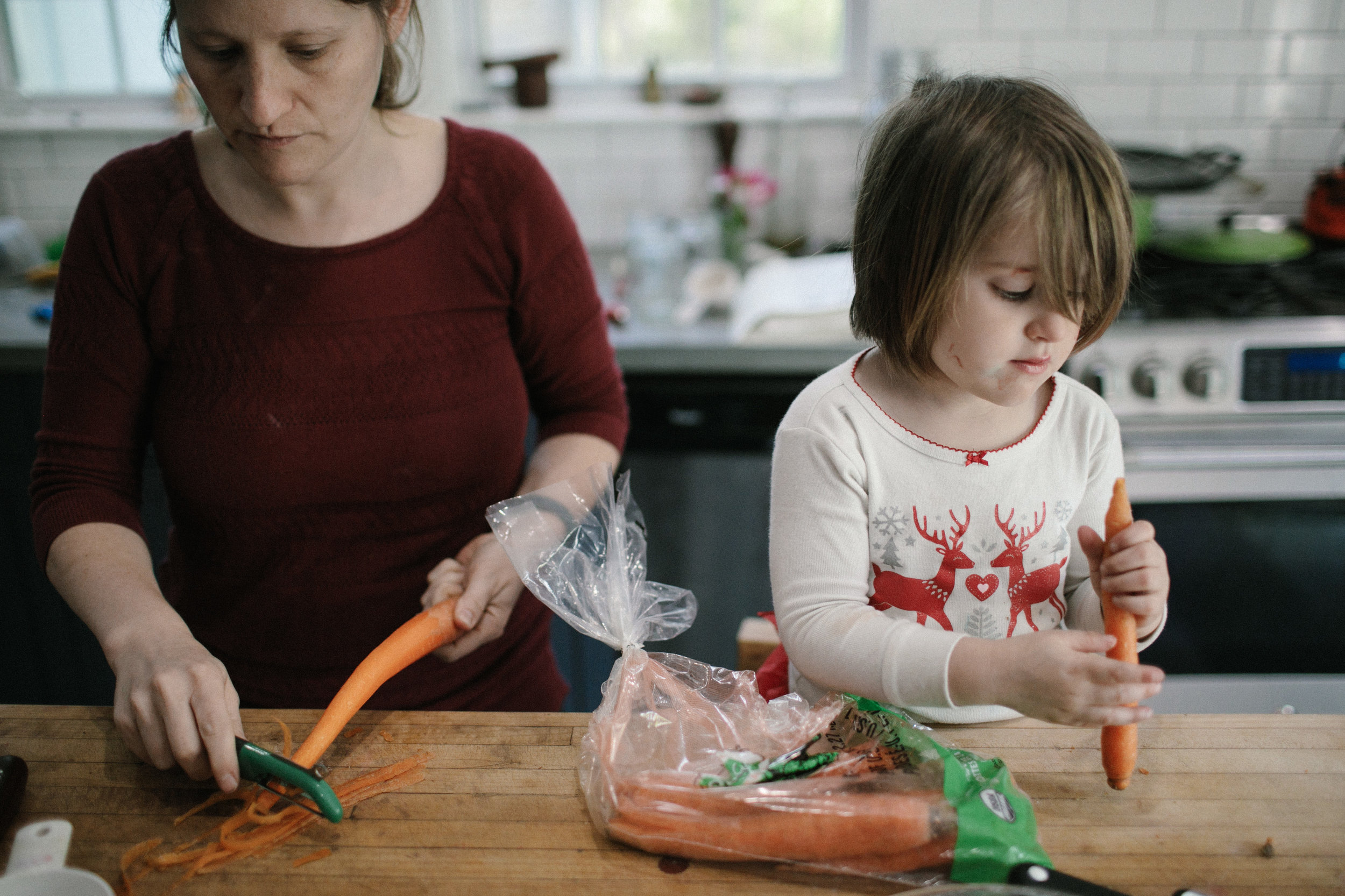 a woman peels a carrot and a girl looks at one