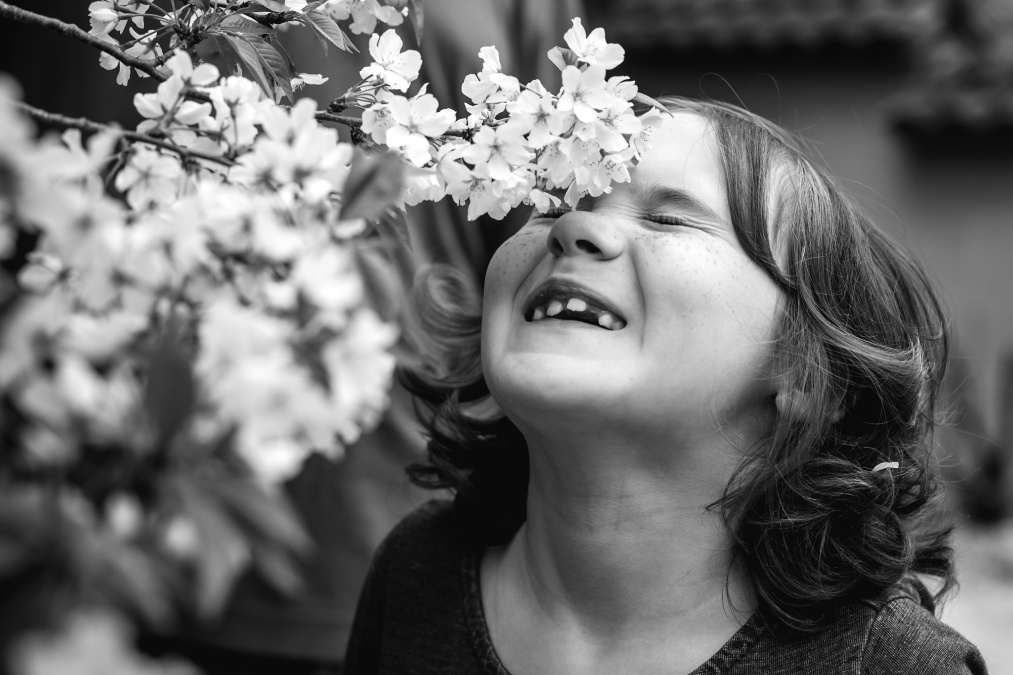 a girl touches her forehead onto some flowers and smiles