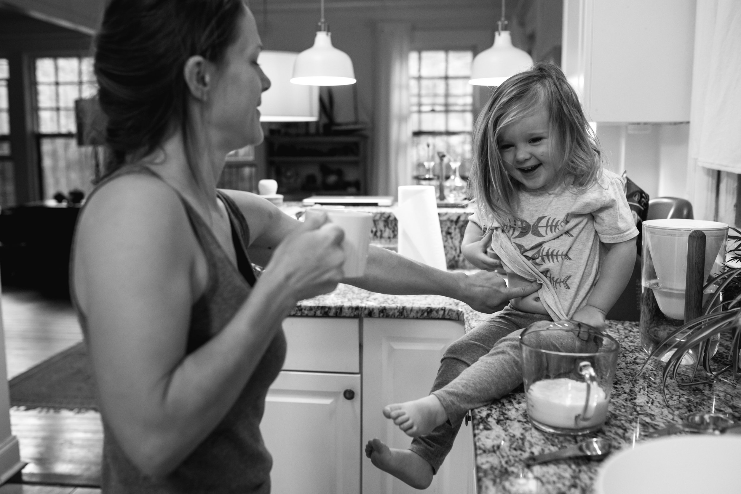 mother tickles daughter's stomach who is sitting on the kitchen counter
