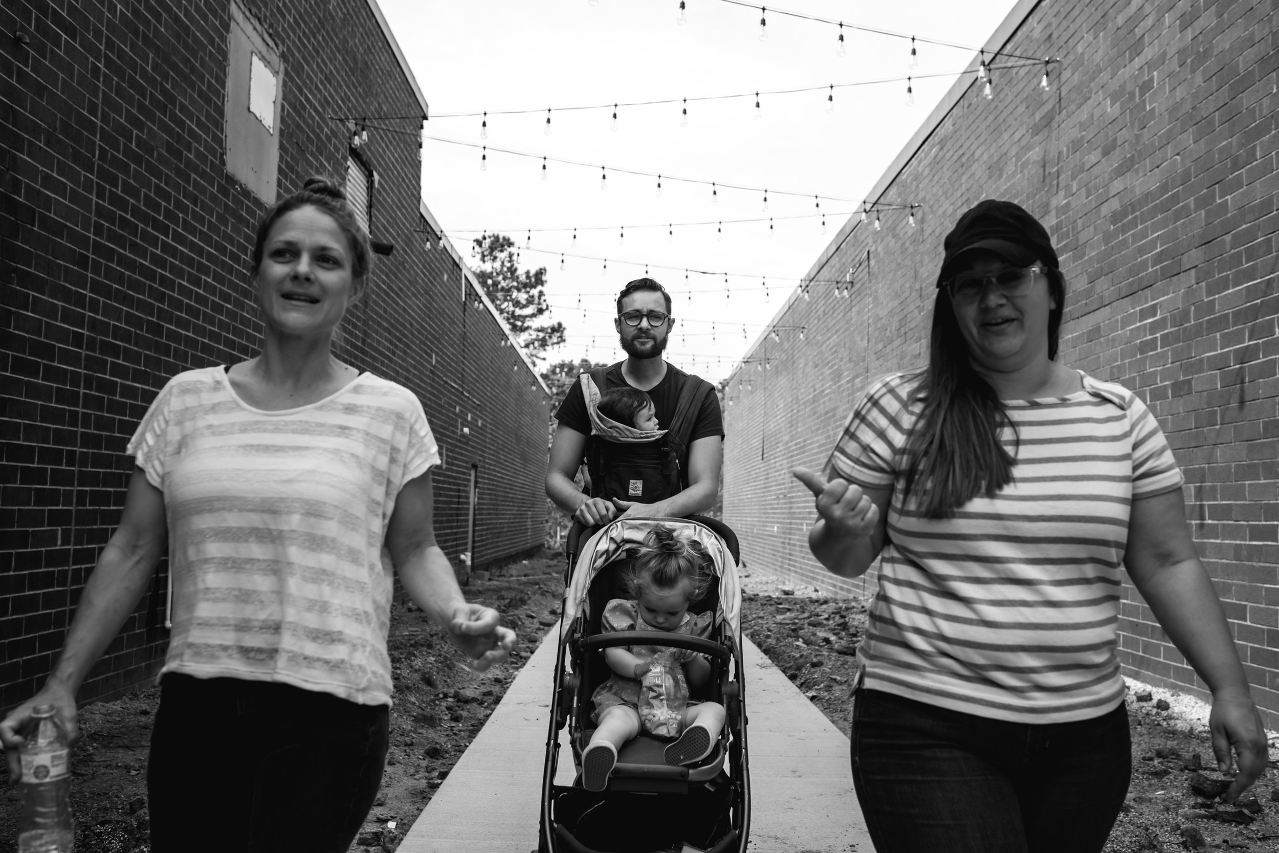 A man pushes a stroller while wearing a baby as two women with striped shirts walk on his sides