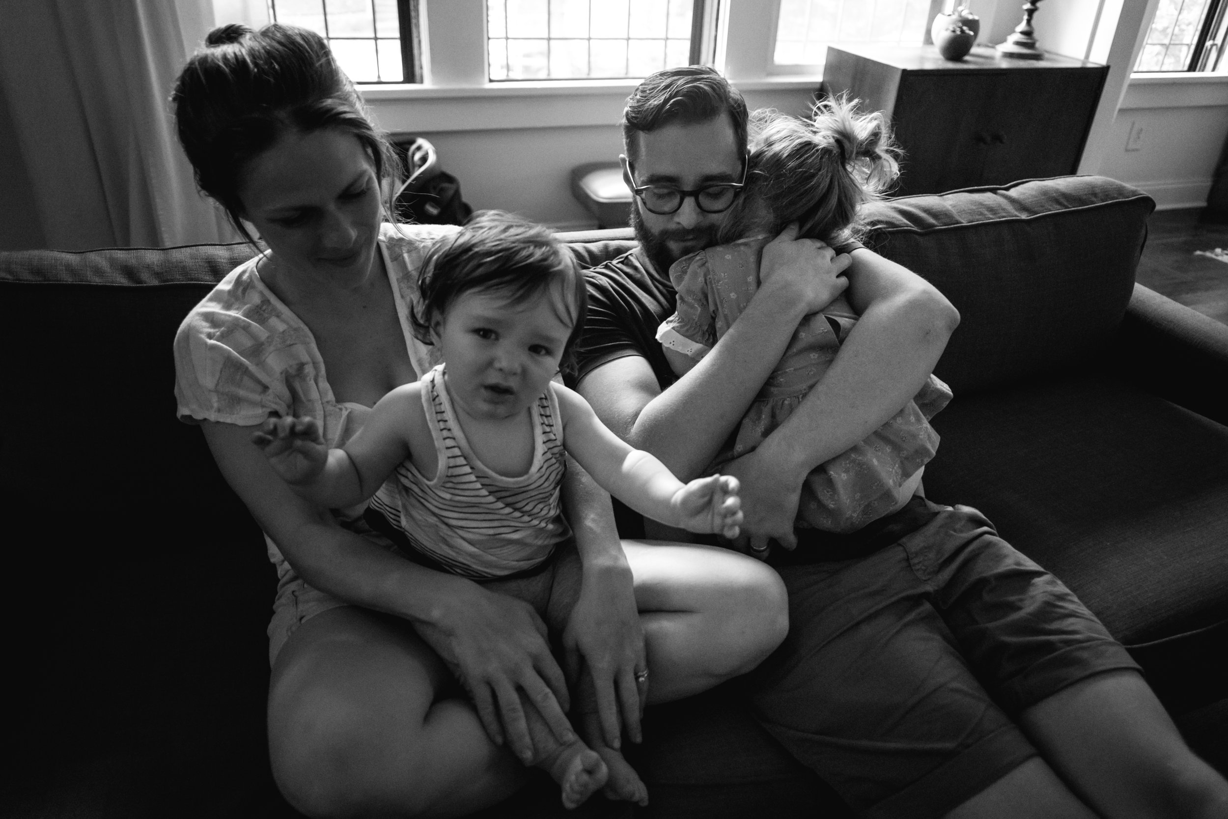 a man embraces his daughter on the couch next to his wife and daughter