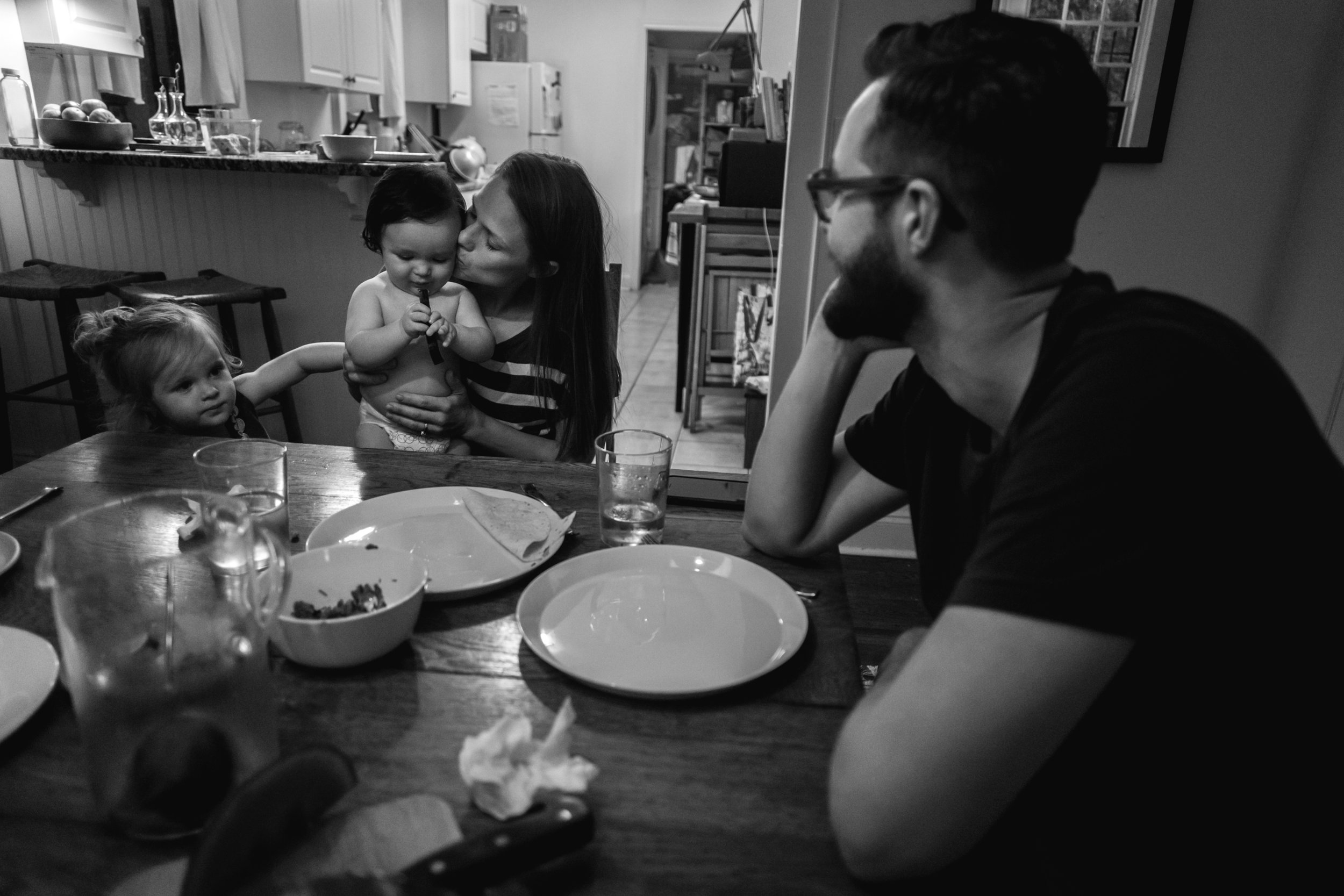 A mother kisses her son's cheek at the table with her daughter and husband watching