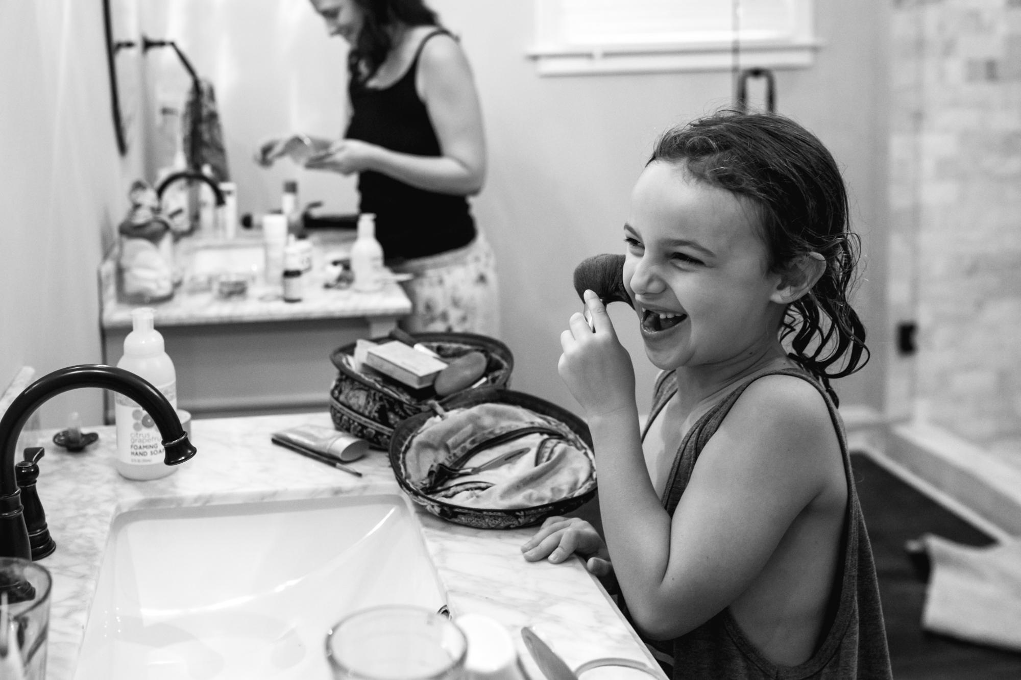 A young girl holds a makeup brush to her cheek and smiles with a toothless smile