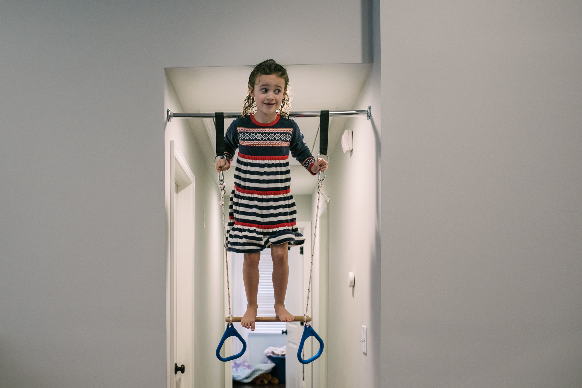Young girl stands on an indoor swing during documentary family photography session