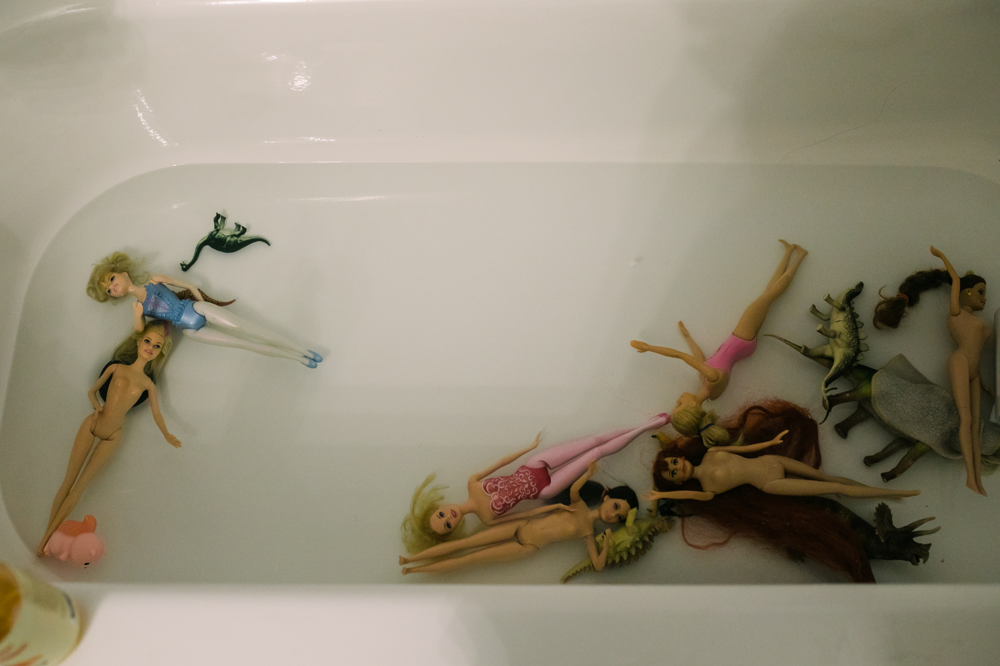 Several Barbies float in bathwater in a bathtub during a documentary family photography session