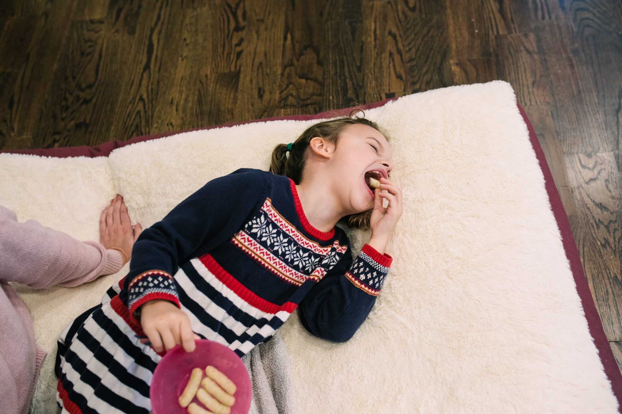 a young girl laughs while eating a snack and lying on a large dog bed during a documentary family photography session