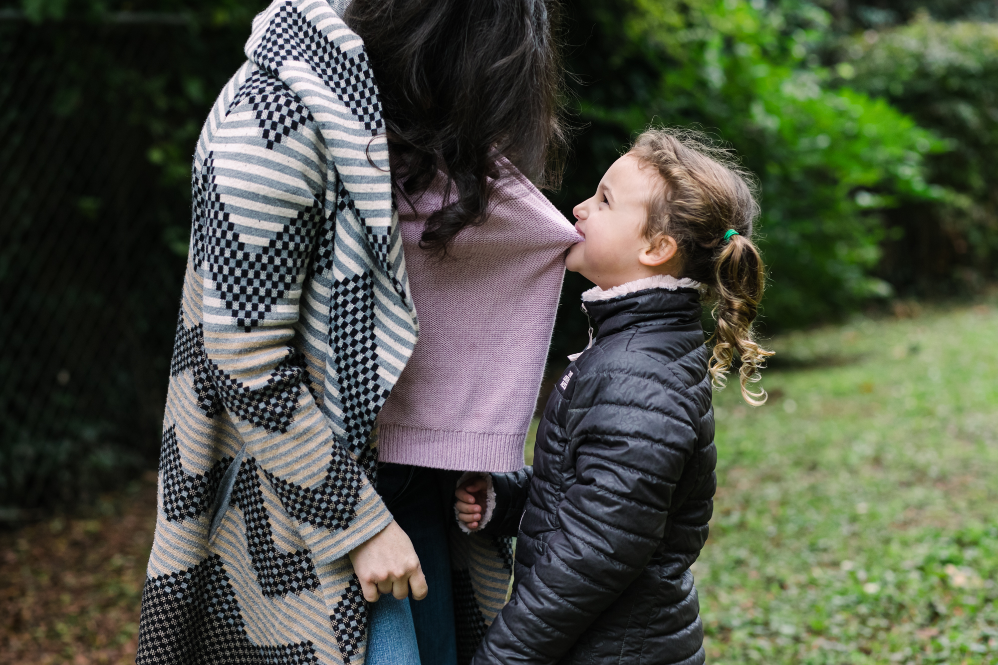 a young girl looks up at her mom as she pulls her shirt with her teeth during a documentary family photography session