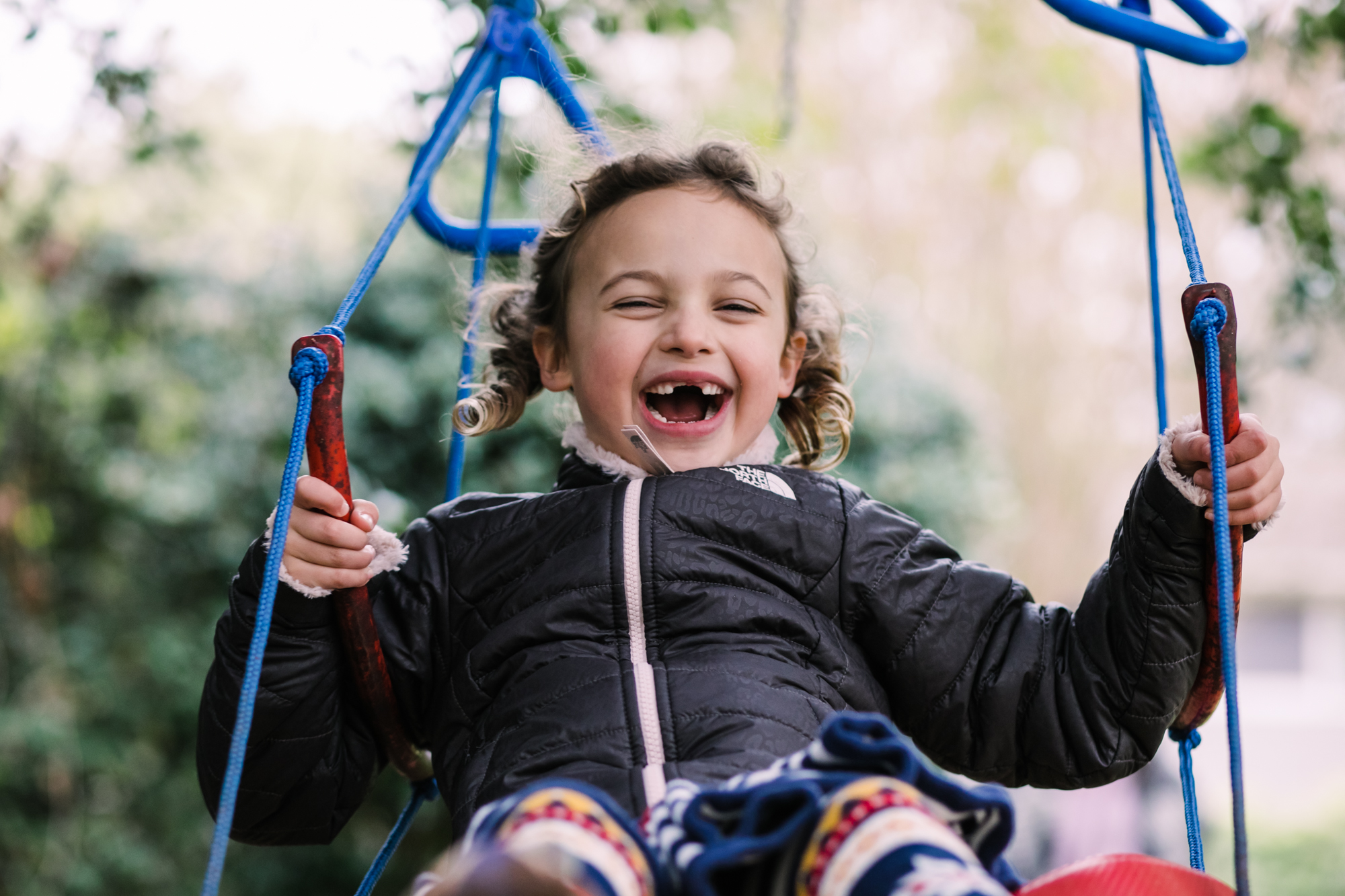 a girl smiles with joy as she swings on a swing during a documentary family photography session
