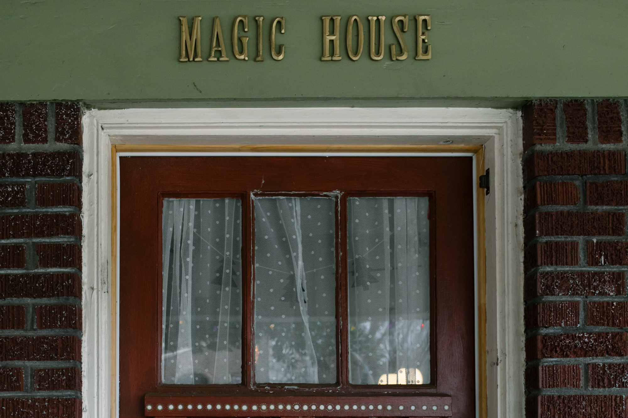 the top of a door with the words Magic House written above the door frame