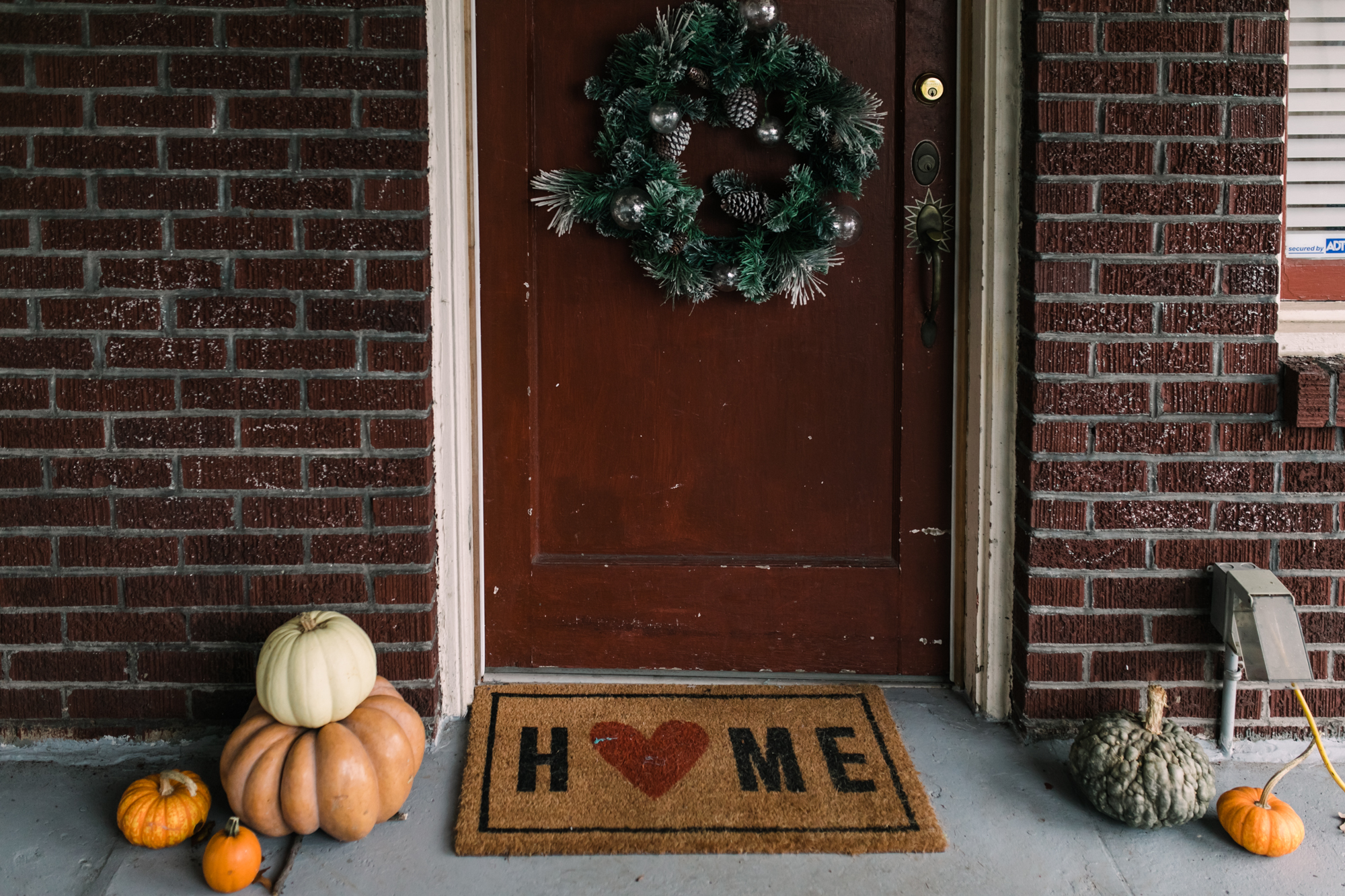 A mat with the word home on it in front of a door that is decorated with a wreath with pumpkins on the ground on the sides of the door