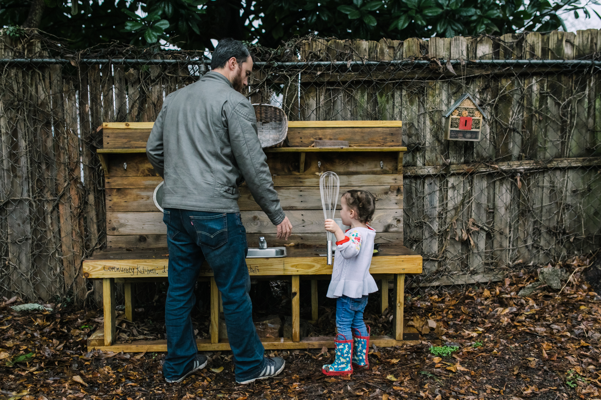 A father and daughter play at an outdoor play kitchen