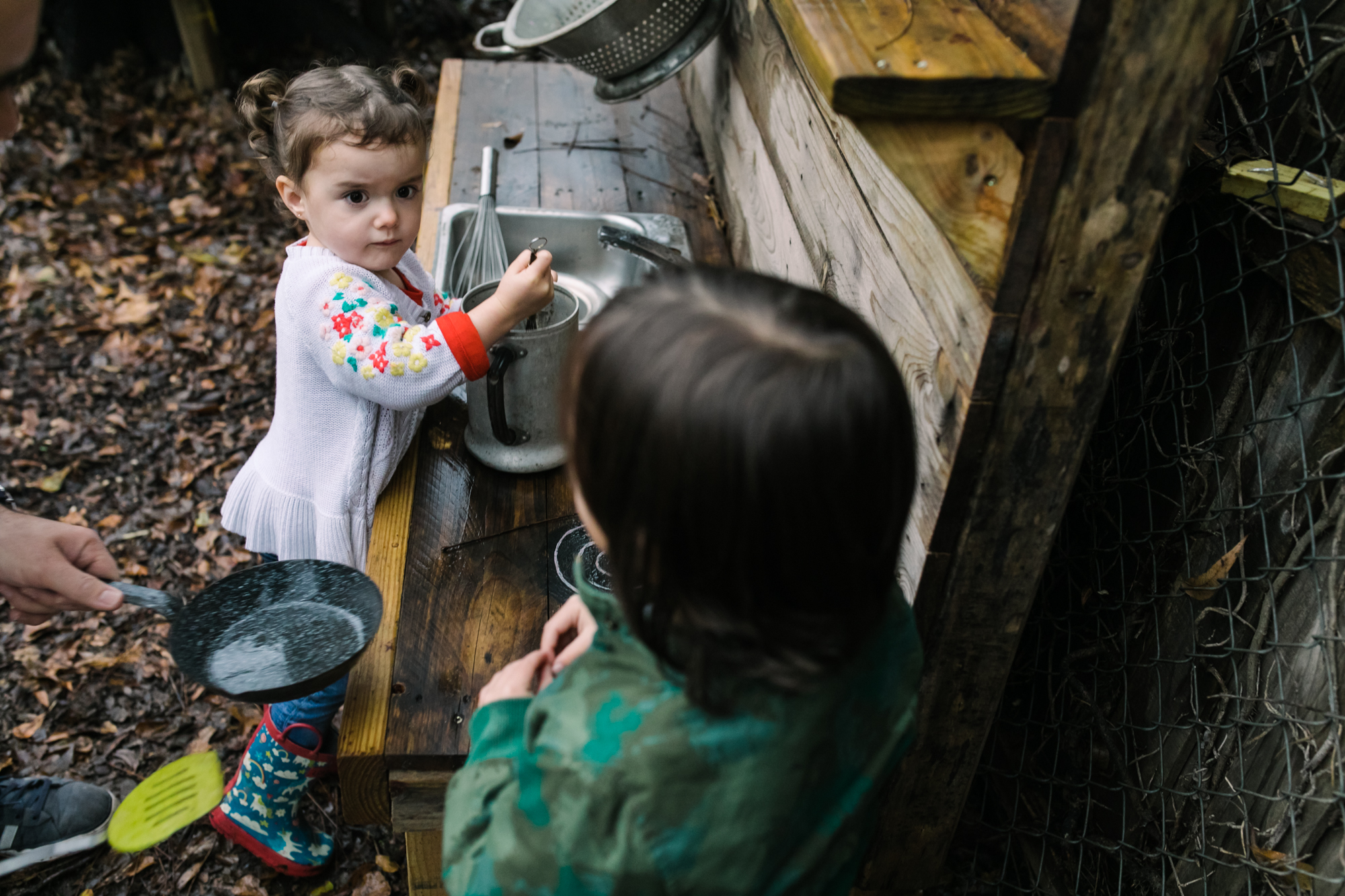 A little girl looks at another child as she mixes something at an outdoor play kitchen