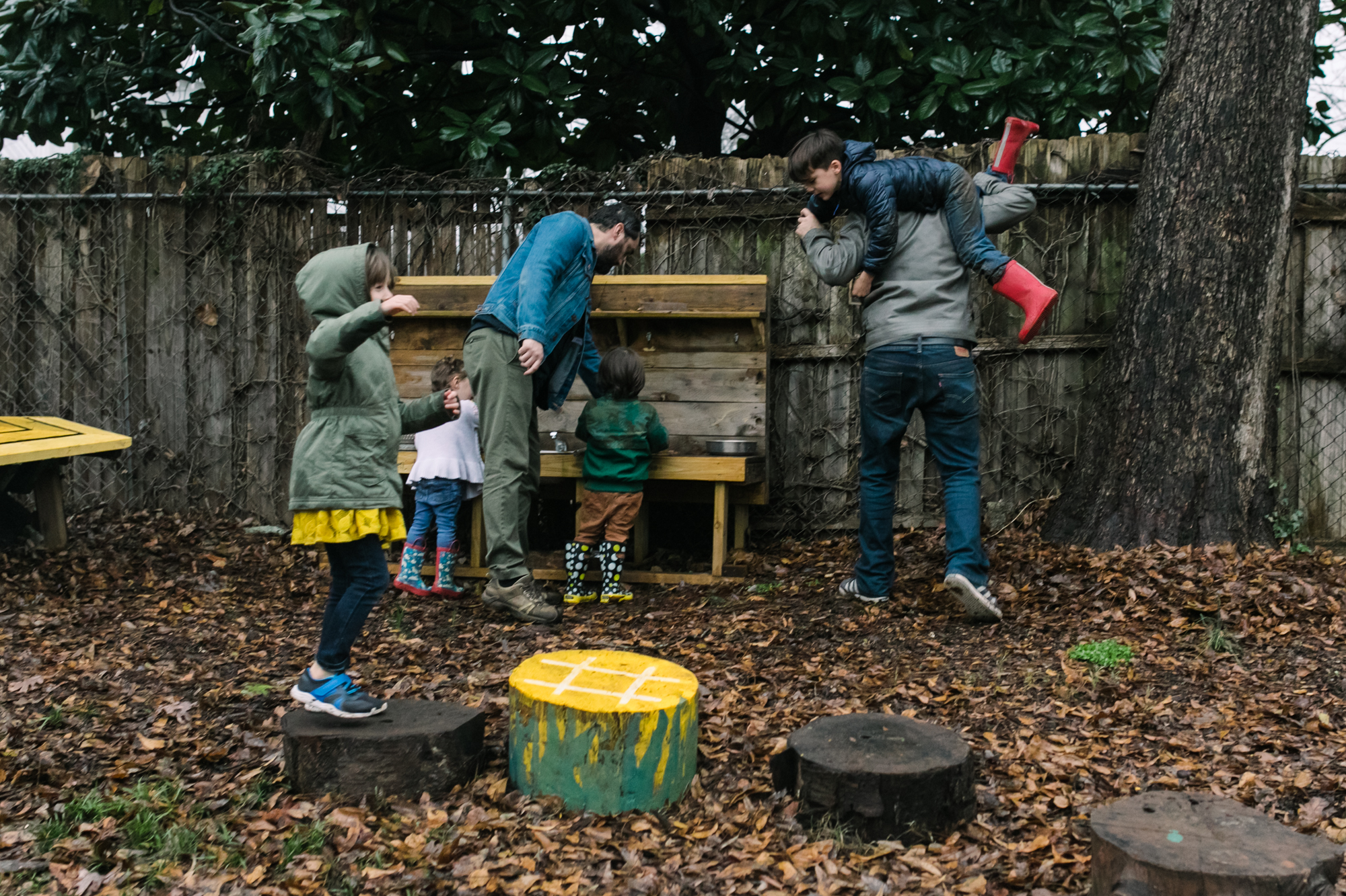 Children play at a play kitchen as a dad holds a boy across his shoulders