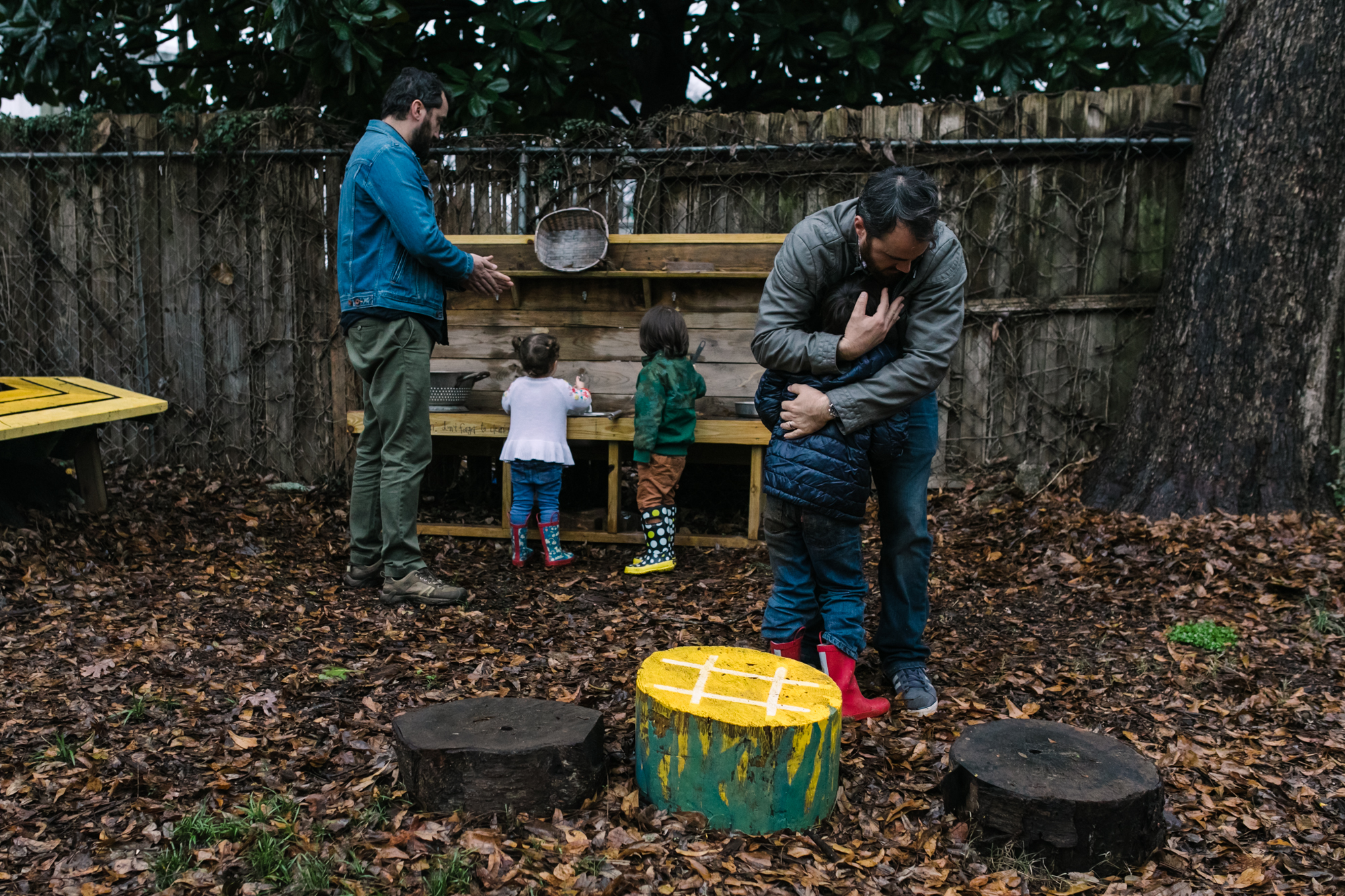 A father comforts his son as two children and a man play at a play kitchen in the background