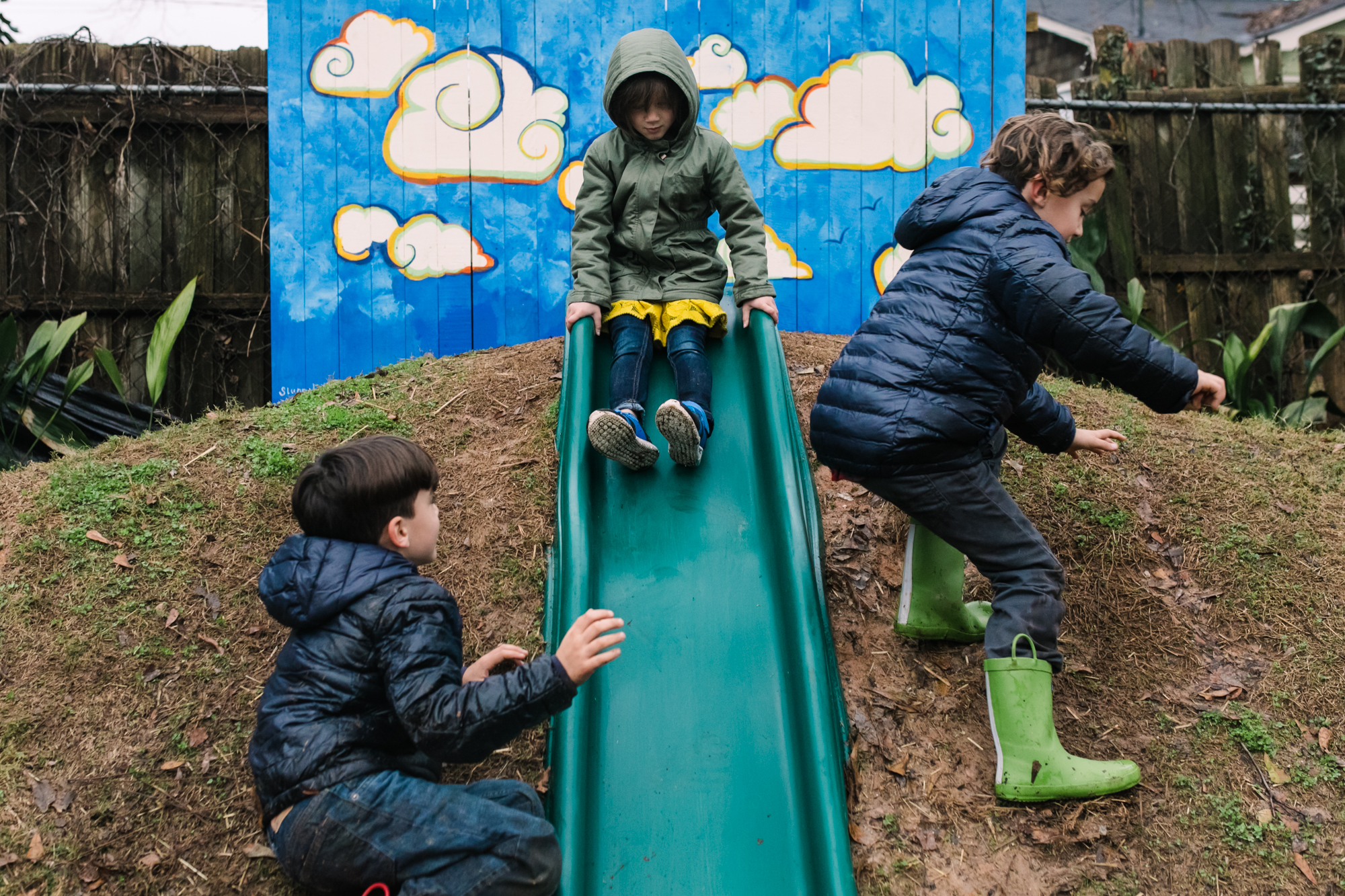 A girl slides down a slide as two boys jump across the slide in front of her