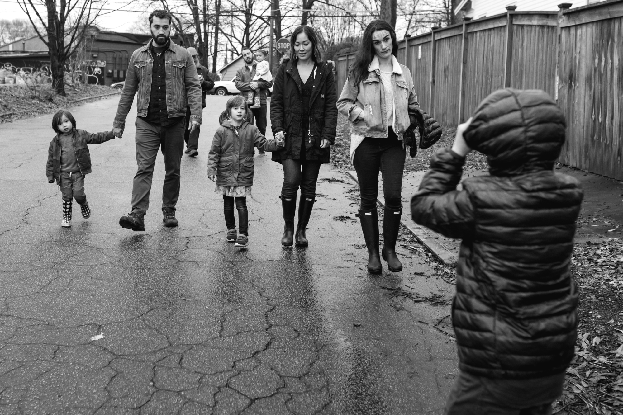 an extended family walks down the street as a mom gives her child who is turned around the mom look