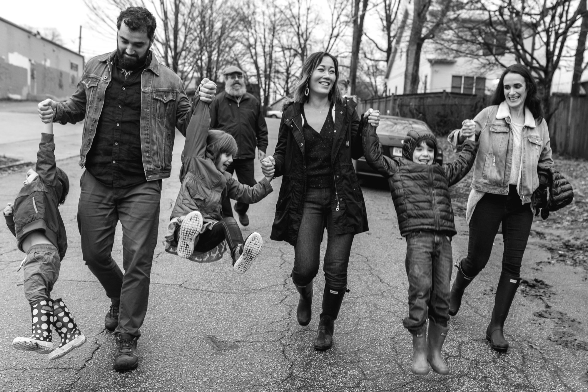 An extended family walks down the street swinging children from their arms