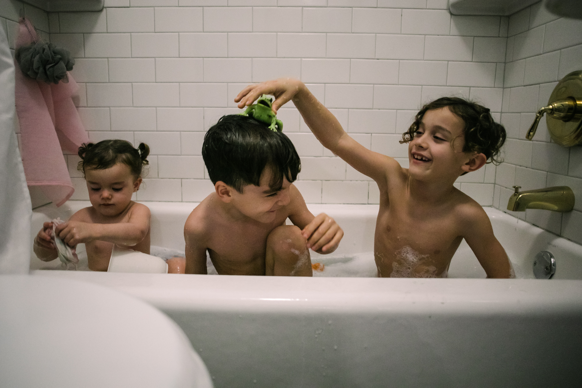 3 siblings take a bath and one child puts a pretend frog on another child's head
