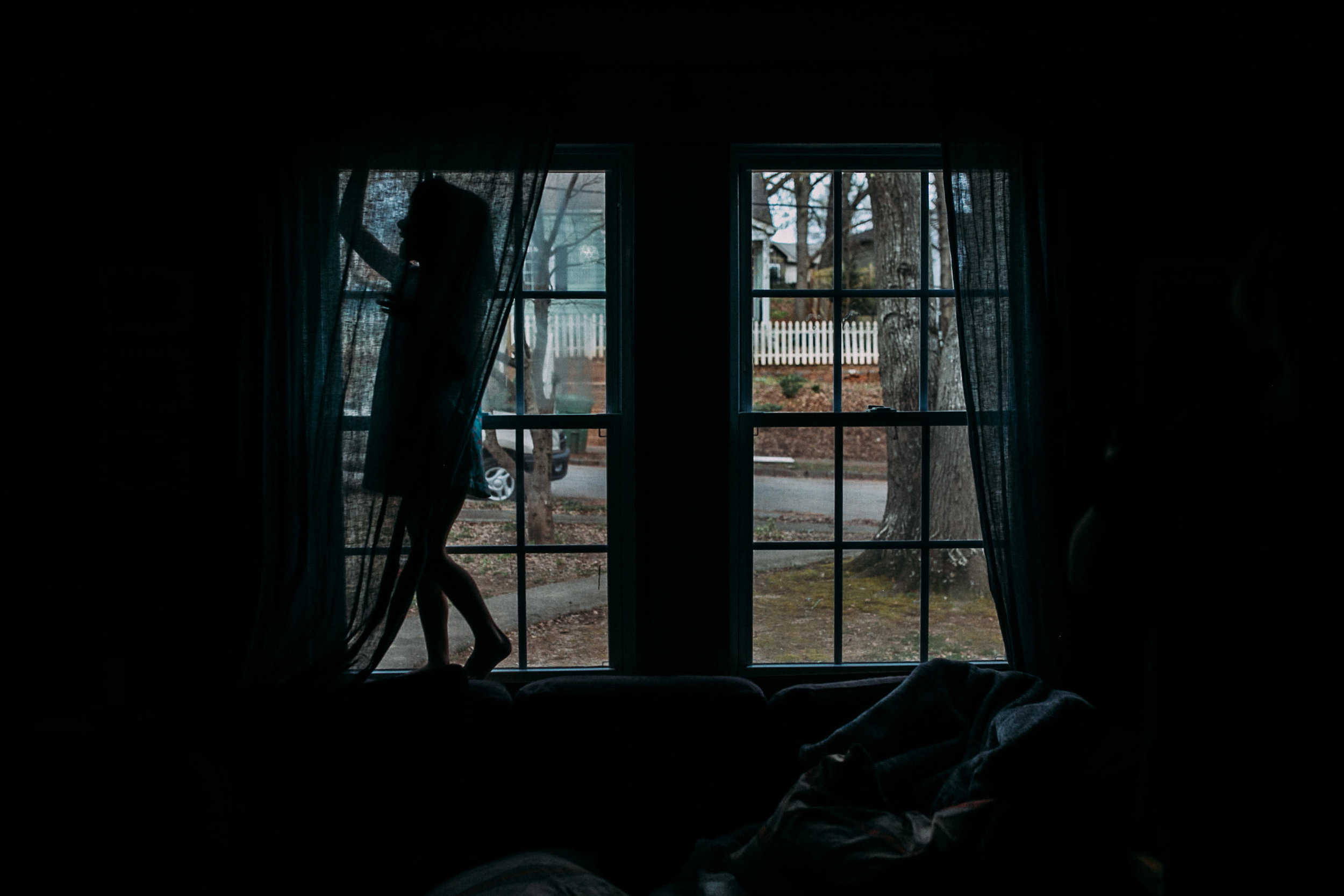 A girl stands in a window behind a curtain