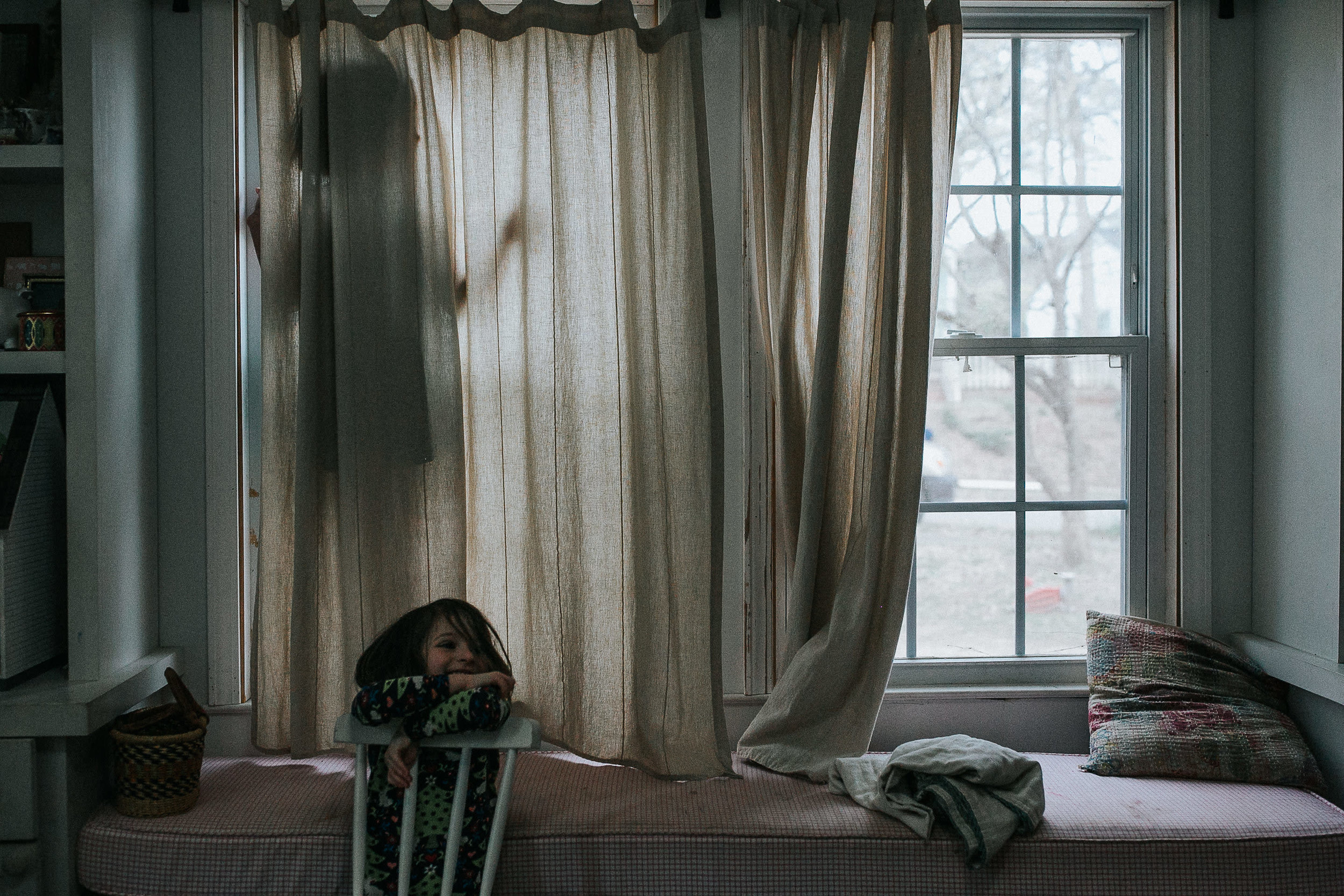 A girl stands in a window behind a curtain and another girl smiles as she leans on a chair in front of the window
