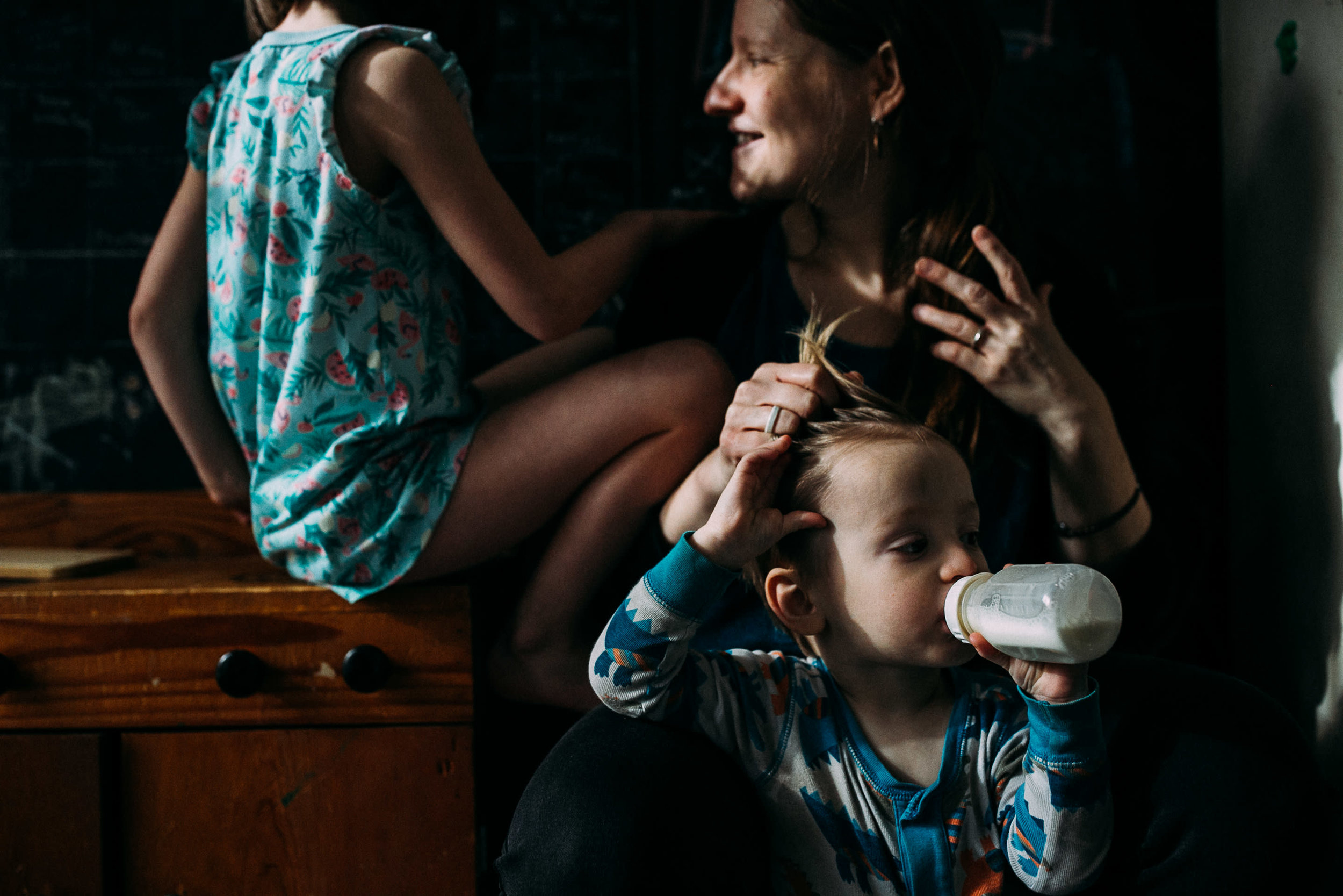 A mother combs her fingers through her toddler's hair while he drinks a bottle and another child sits nearby