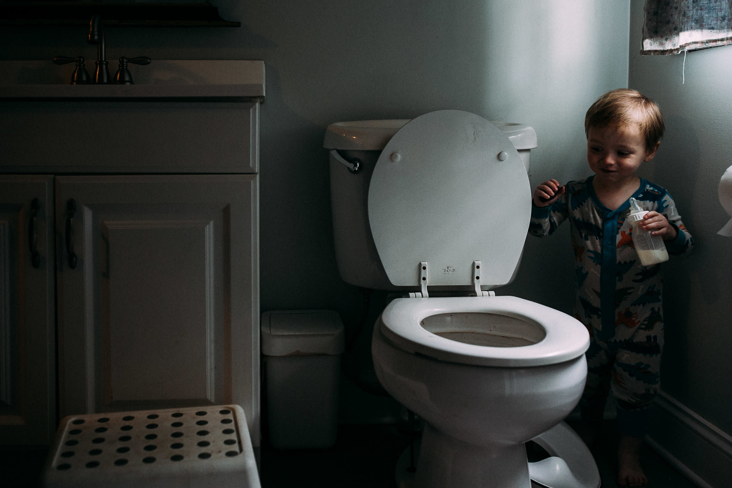 A toddler stands near a dirty toilet holding a bottle
