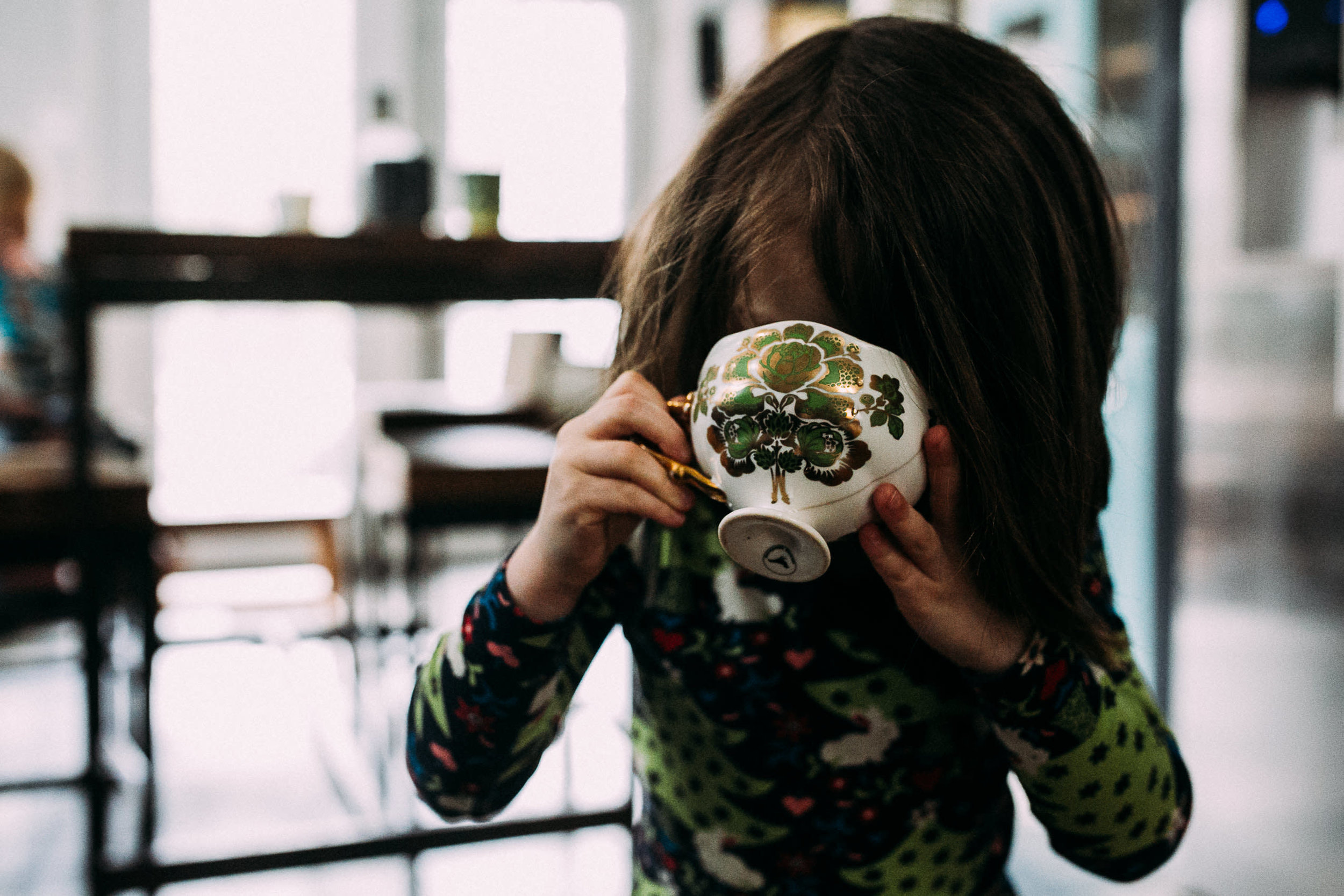 A girl drinks from a green floral teacup