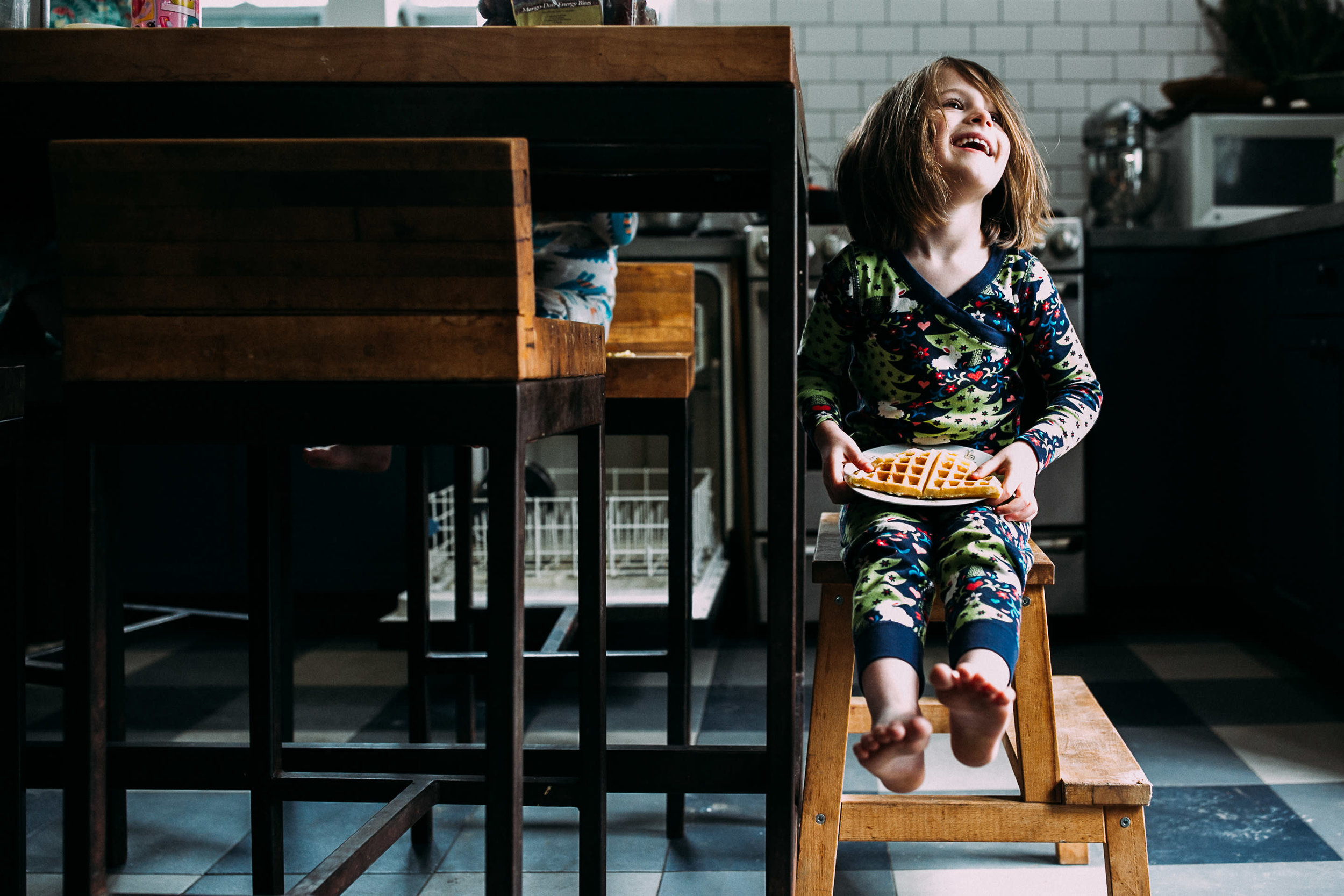 A girl sits on a stool and holds a waffle in her lap while looking up and smiling