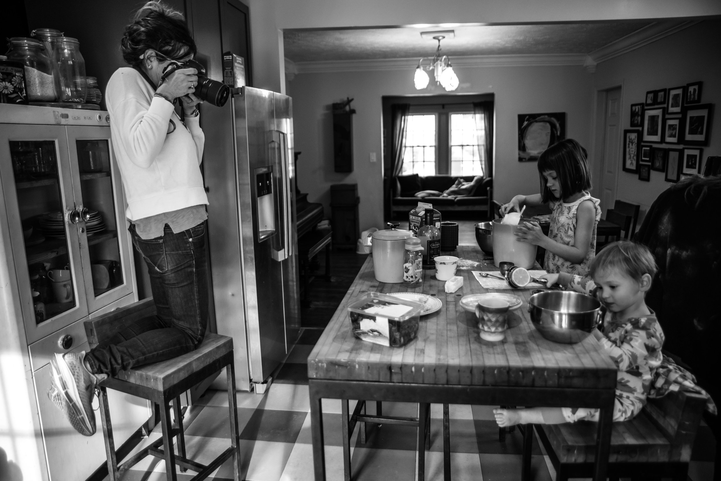 a photographer kneels on a chair and takes a picture of kids at the table making waffles