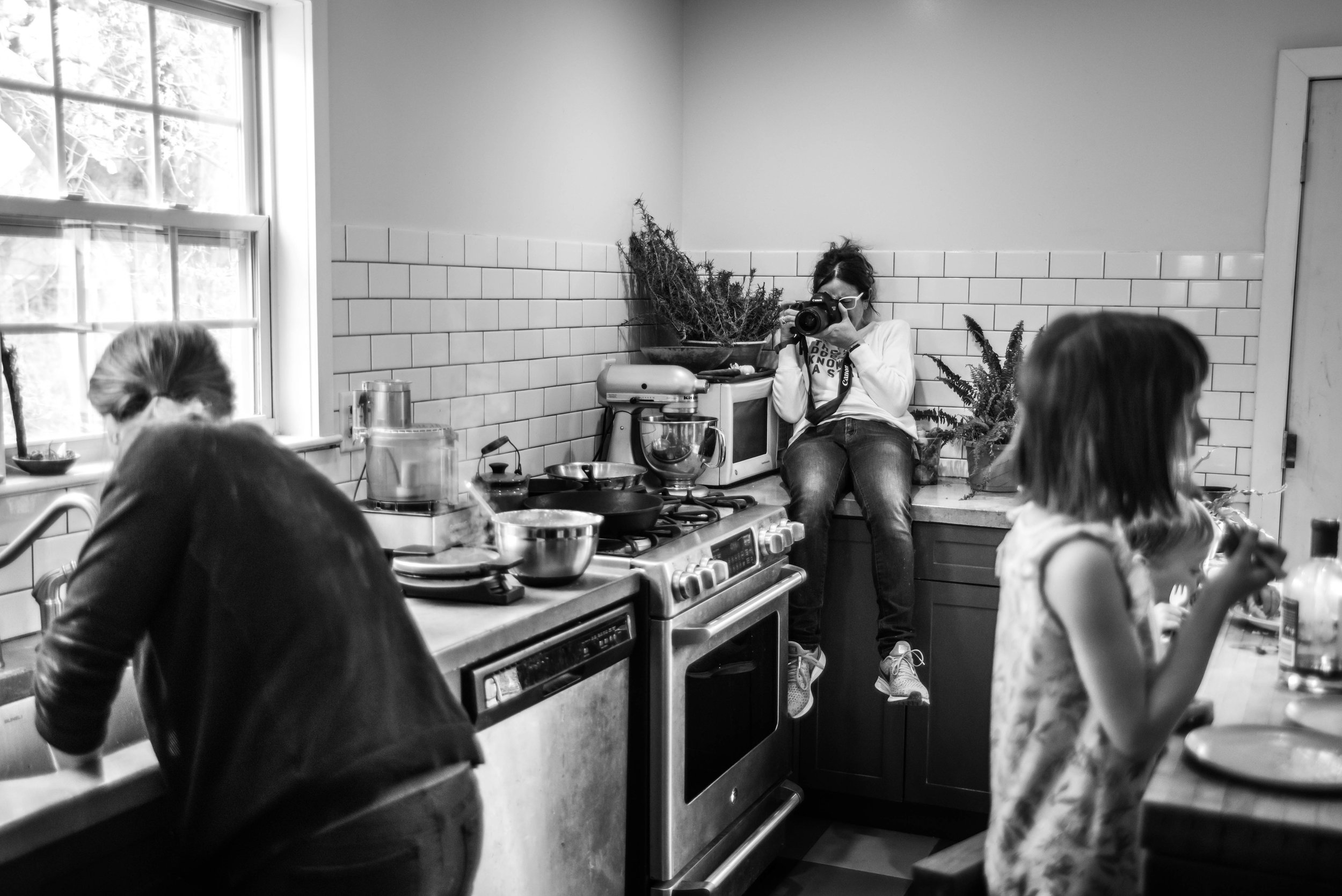 a photographer sits on a counter and photographs a mother doing the dishes