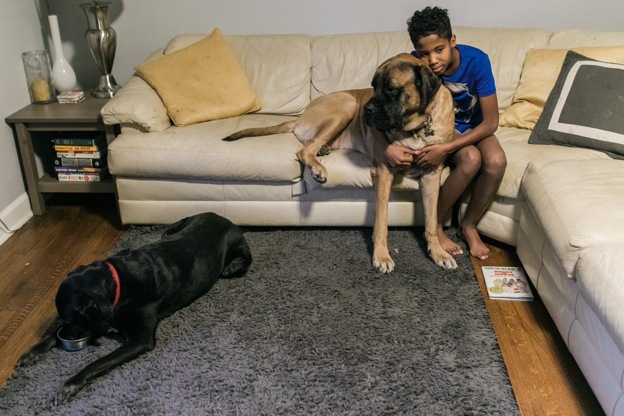 A boy sits on a couch with his arms around a large dog