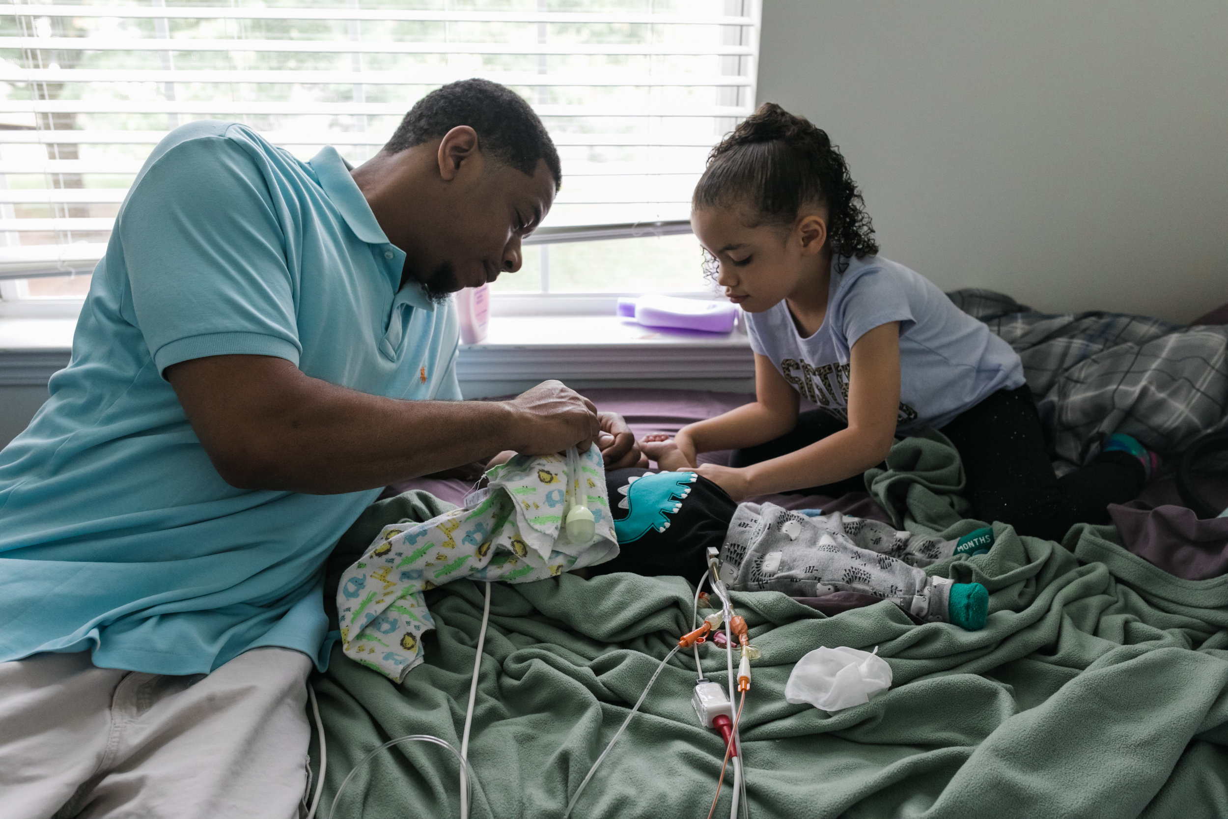 a father and his older daughter care for a baby boy