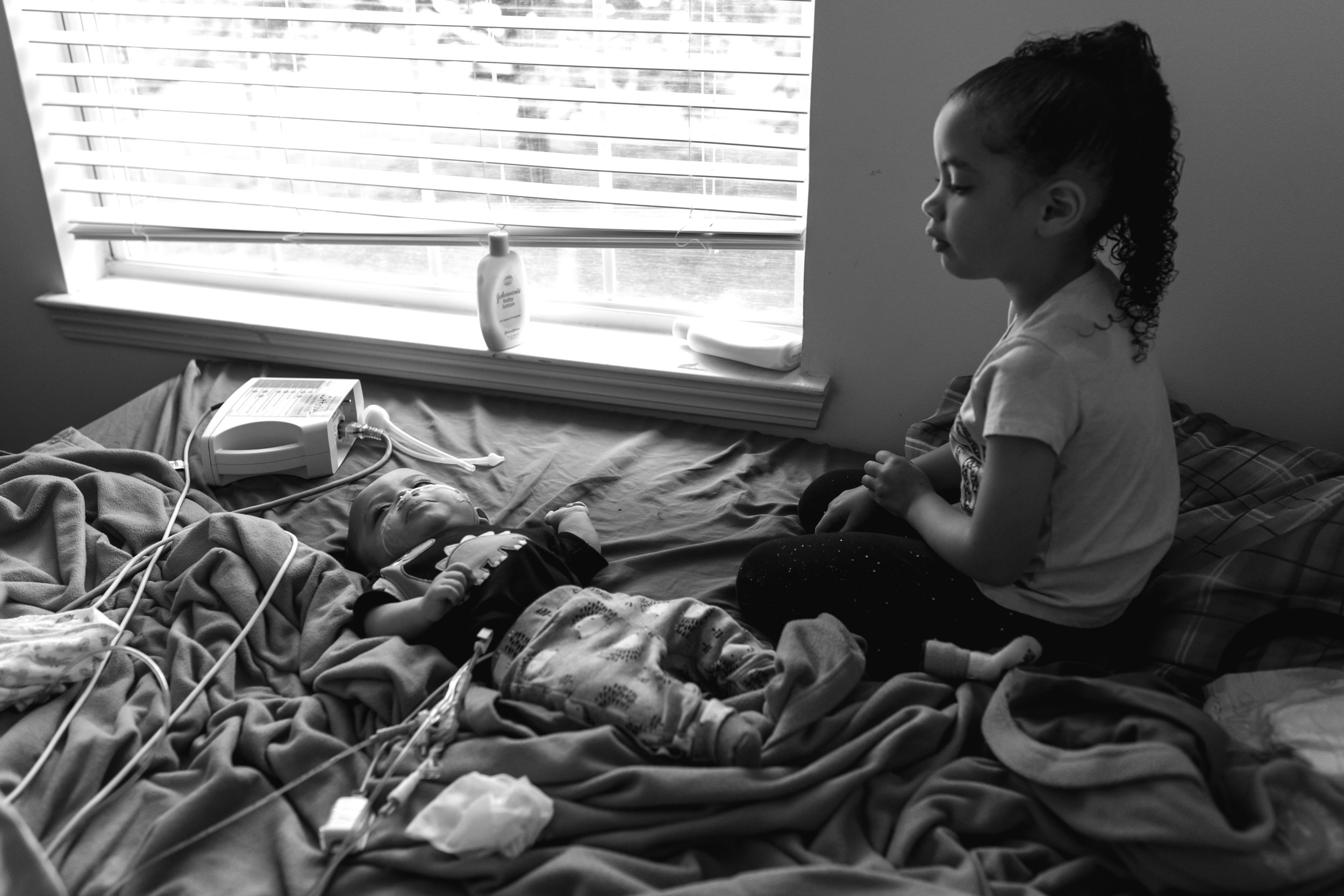 a girl sits on a bed looking at her baby brother