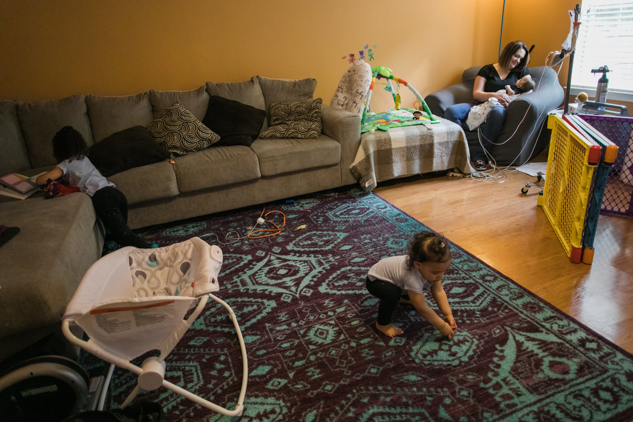 A mother holds her infant son in the corner of a living room as her two daughters play on their own