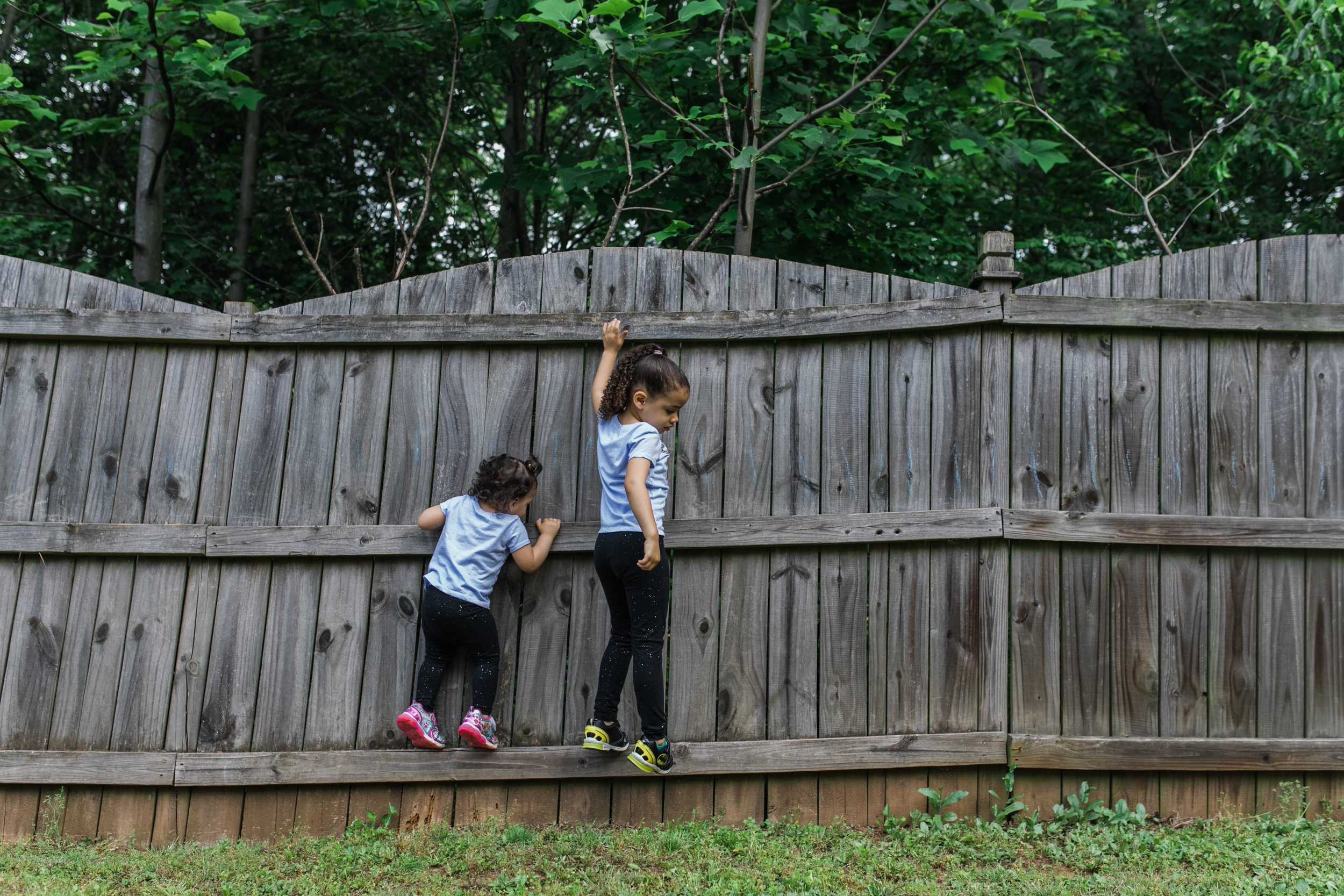 two girls climb on a fence