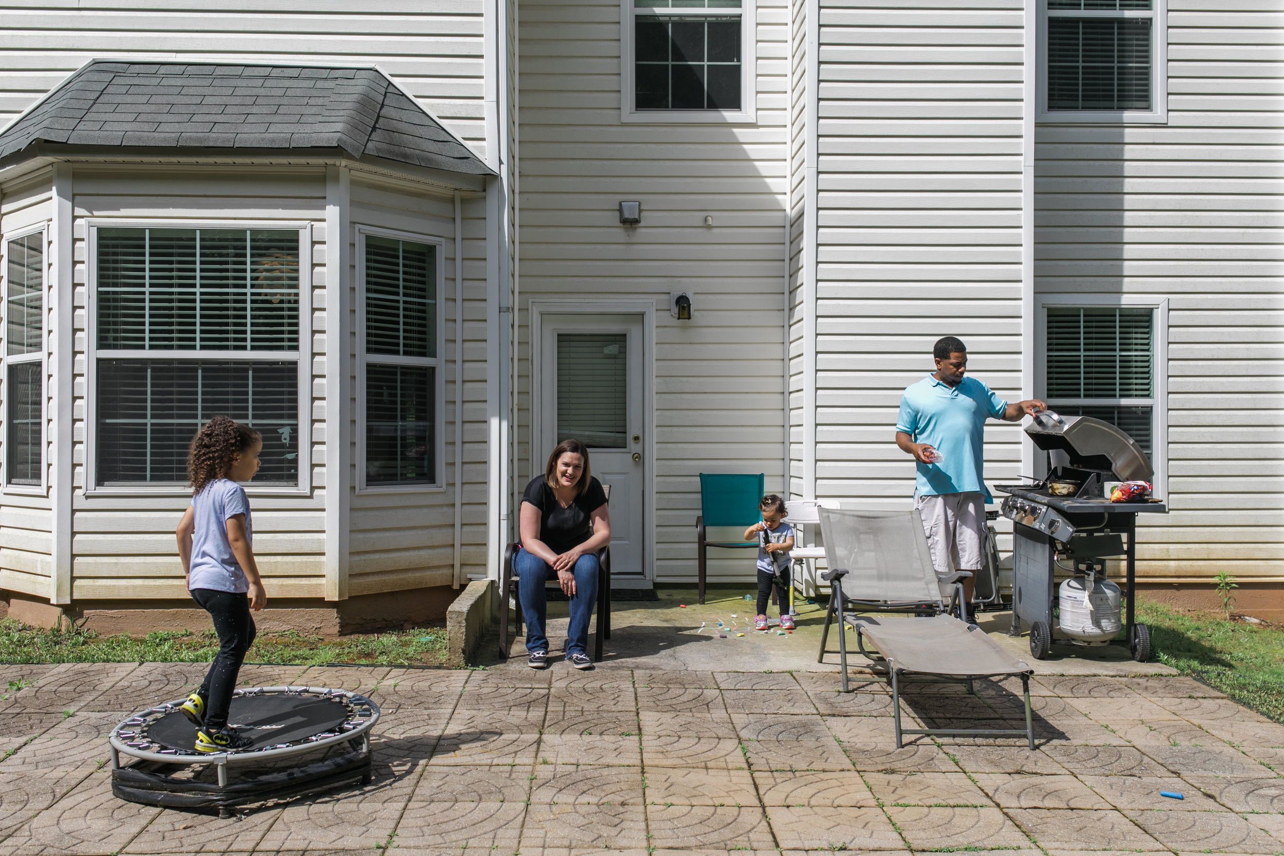 a father holds open a grill and a mother sits on a chair as they watch their daughters play in their backyard