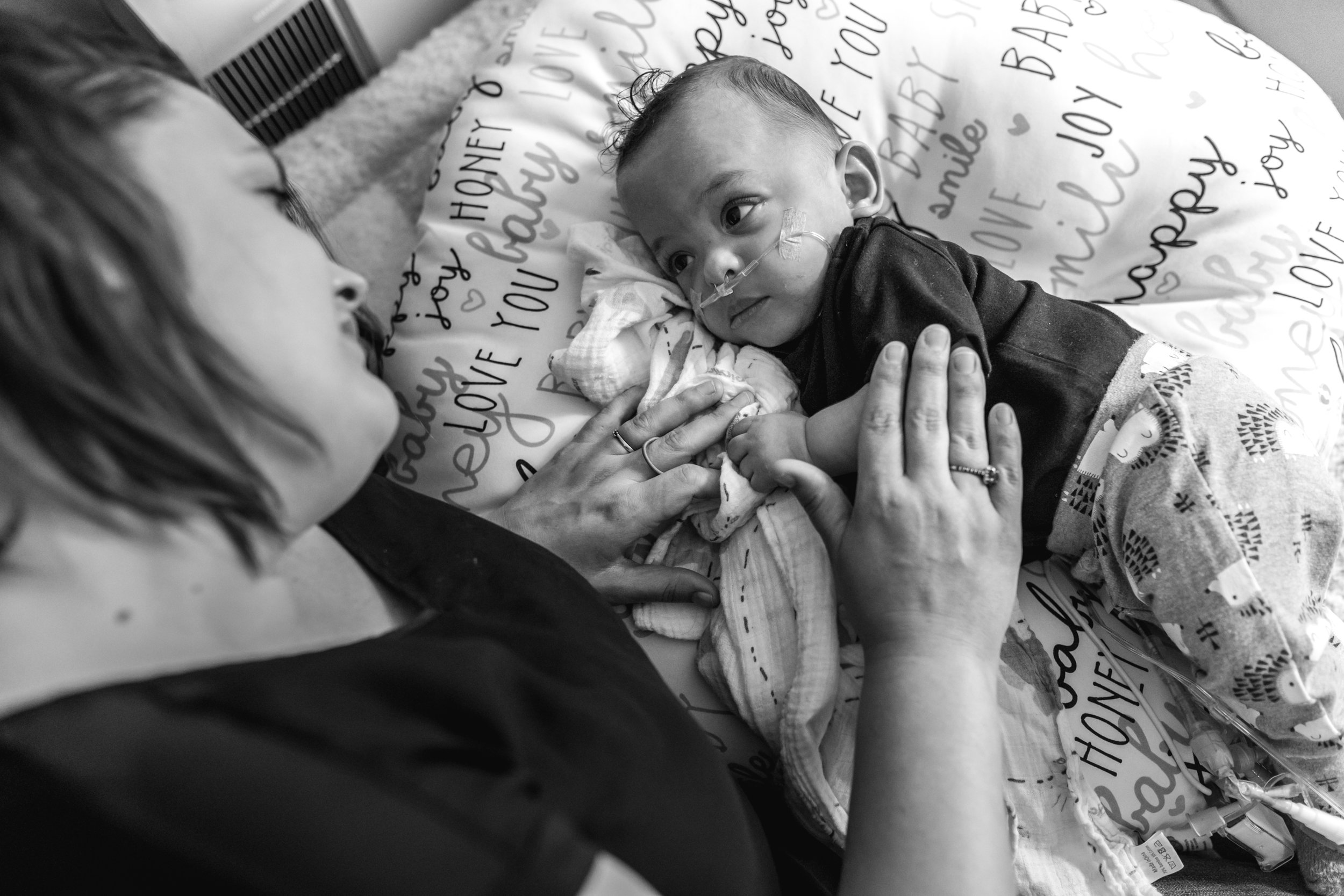 An infant boy looks up at his mom who has her hand on him